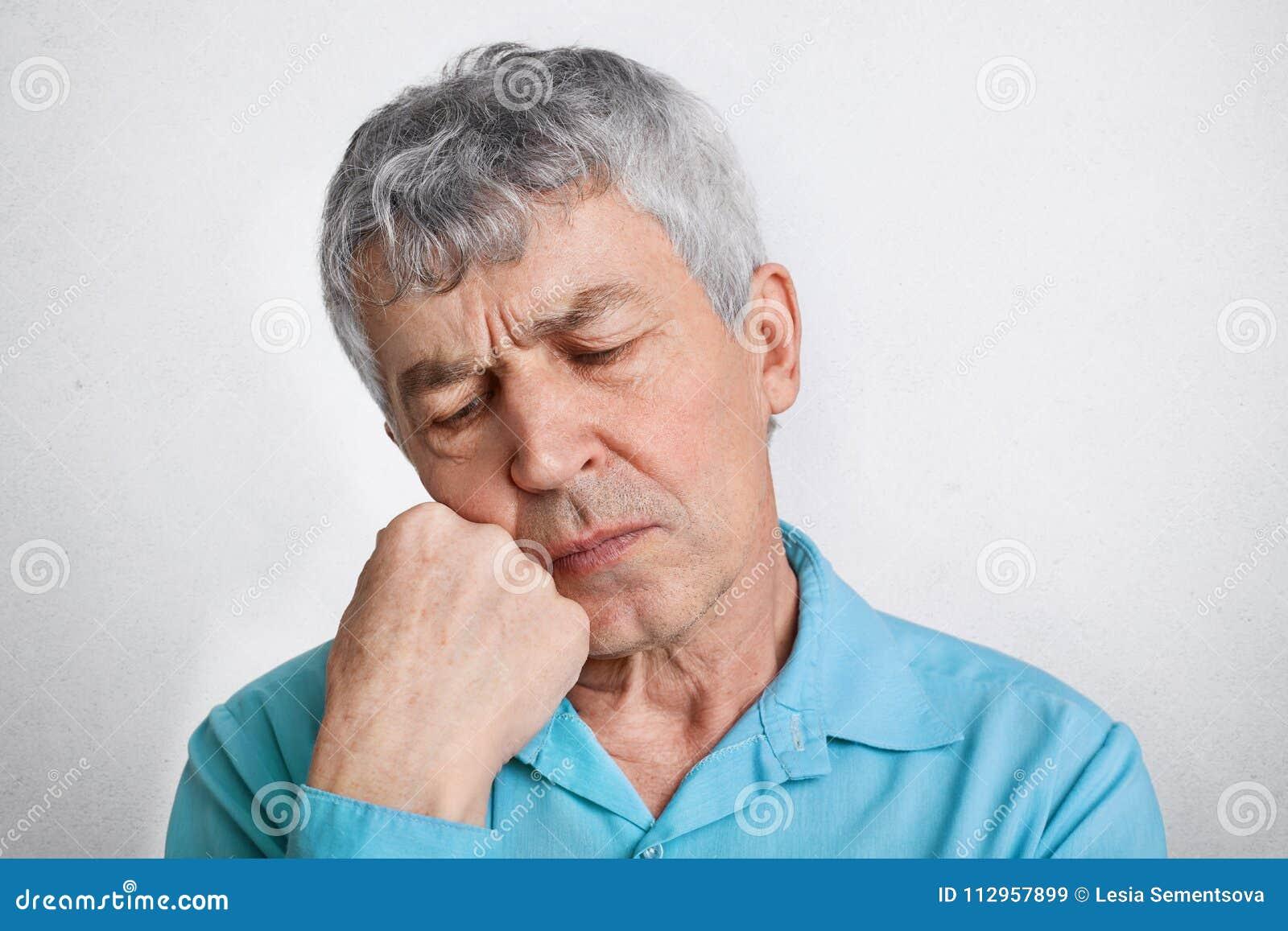 Το στοχαστικό ηλικιωμένο αρσενικό με τη σκεπτική έκφραση, αισθάνεται μόνο, κρατά το χέρι κάτω από το πηγούνι και συλλογίζεται για