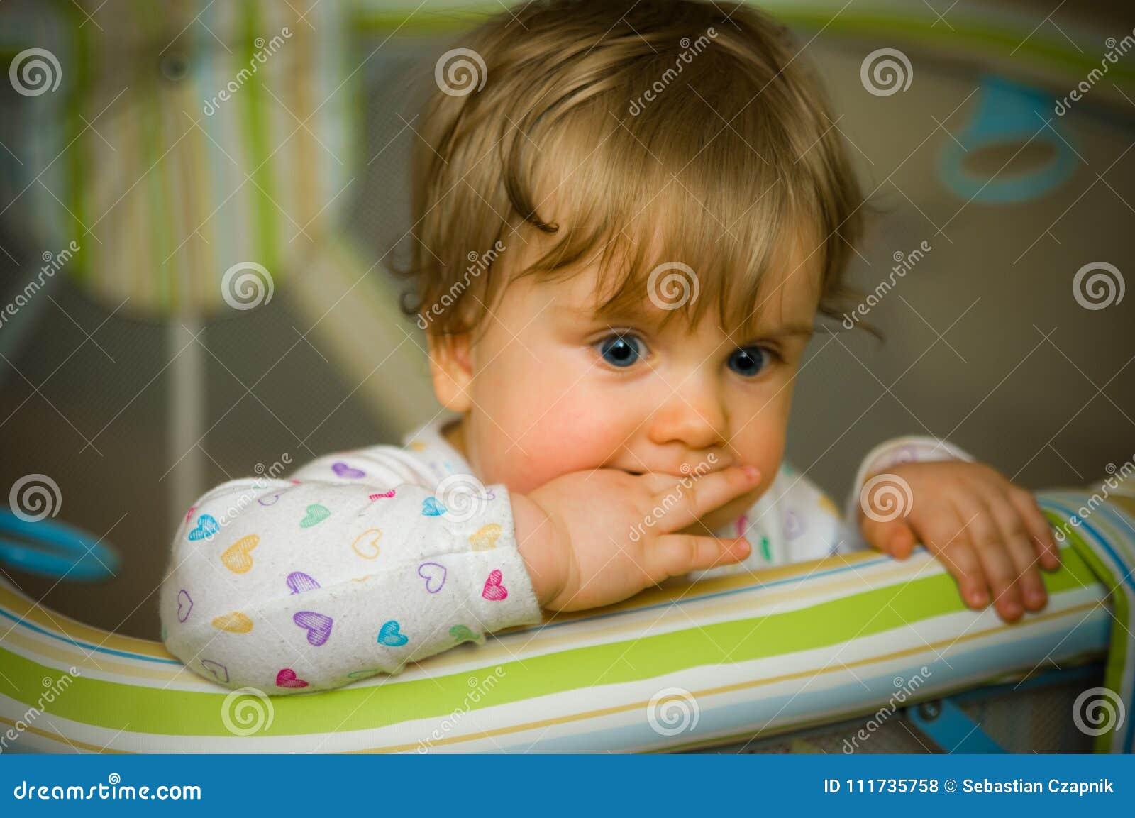Το στοχαστικό μωρό μέσα το δάγκωμα των δάχτυλών της