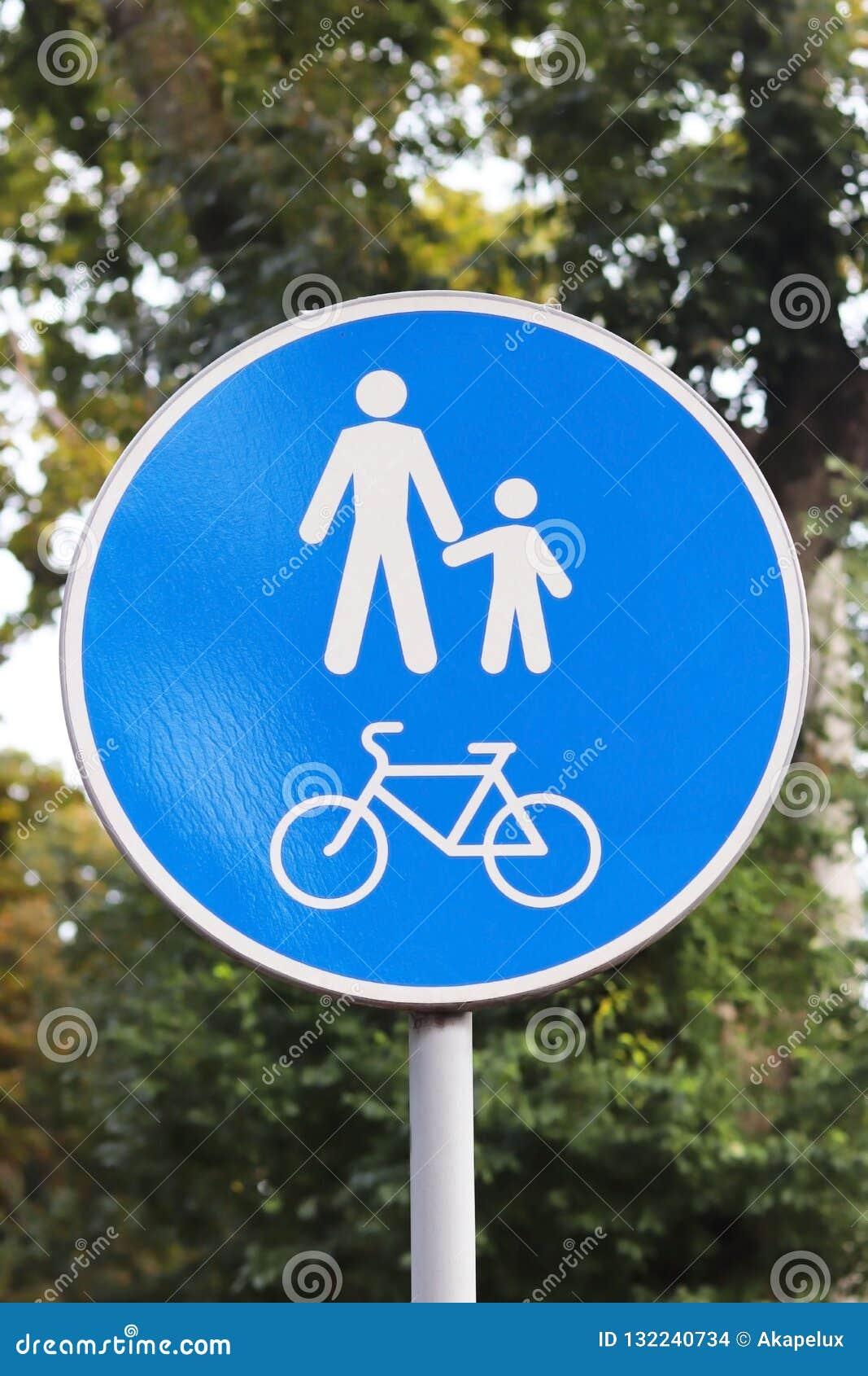 Το στρογγυλός-διαμορφωμένο οδικό σημάδι είναι μια ζώνη πεζών και ποδηλάτων σε ένα κλίμα του πράσινου φυλλώματος Οι λευκοί άνθρωπο
