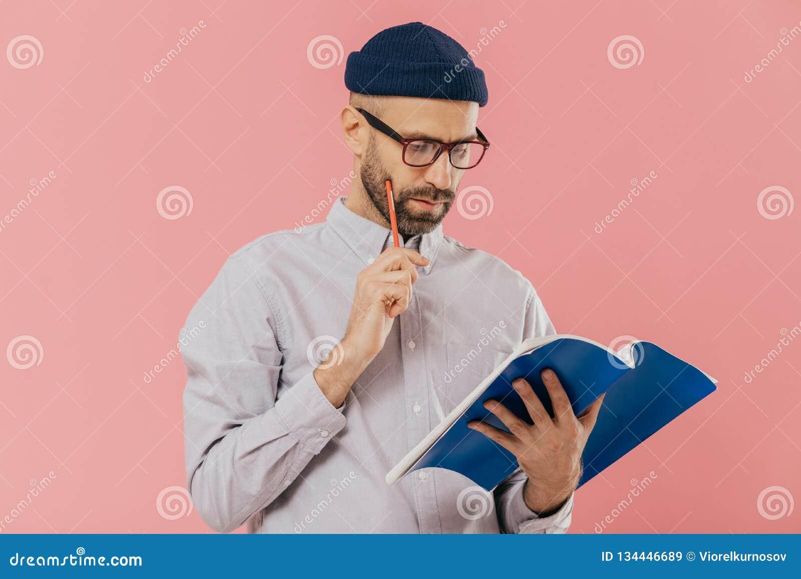 Το συγκεντρωμένο αξύριστο ενήλικο άτομο κρατά το μπλε εγχειρίδιο και το μολύβι, διαβάζει τις απαραίτητες πληροφορίες, έχει τη σοβ