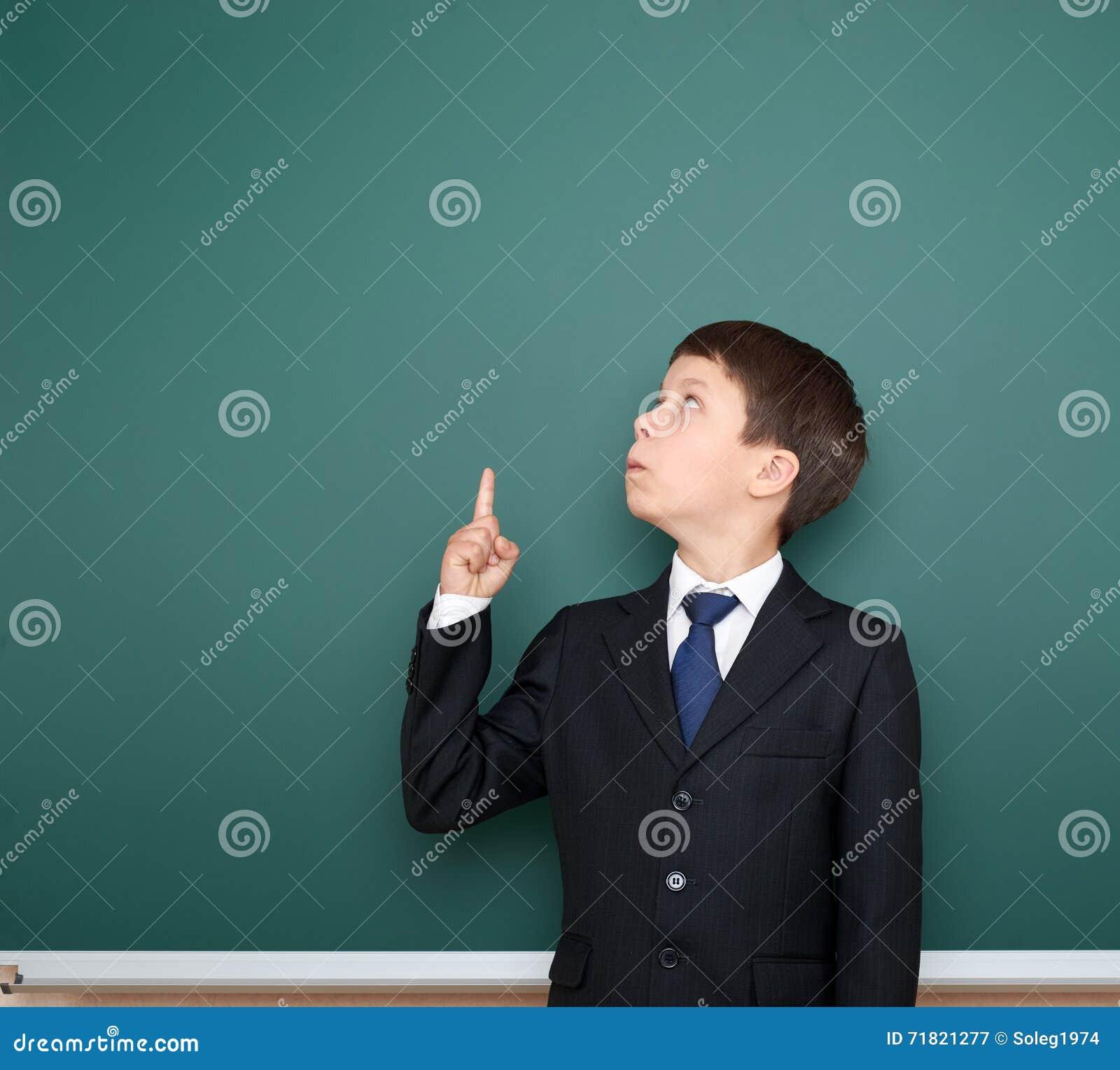 Το σχολικό αγόρι στο μαύρο κοστούμι παρουσιάζει δάχτυλο επάνω στη χειρονομία και αναρωτιέται, δείχνει στο πράσινο υπόβαθρο πινάκω