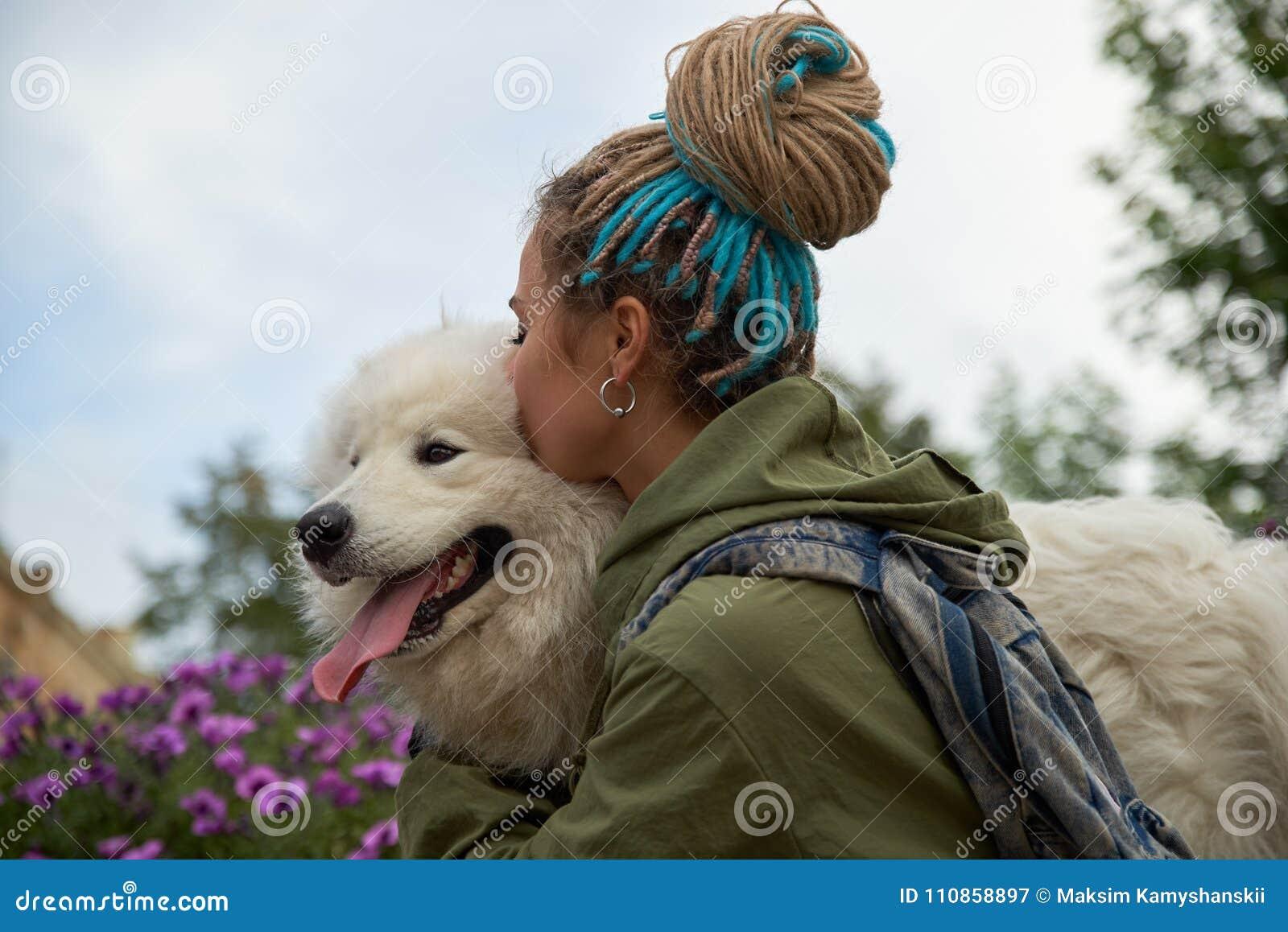 Το σύγχρονο μοντέρνο νέο κορίτσι με τα dreadlocks στο κεφάλι της αγκαλιάζει και φιλά το αγαπημένο σκυλί της λευκό σαν το χιόνι Sa