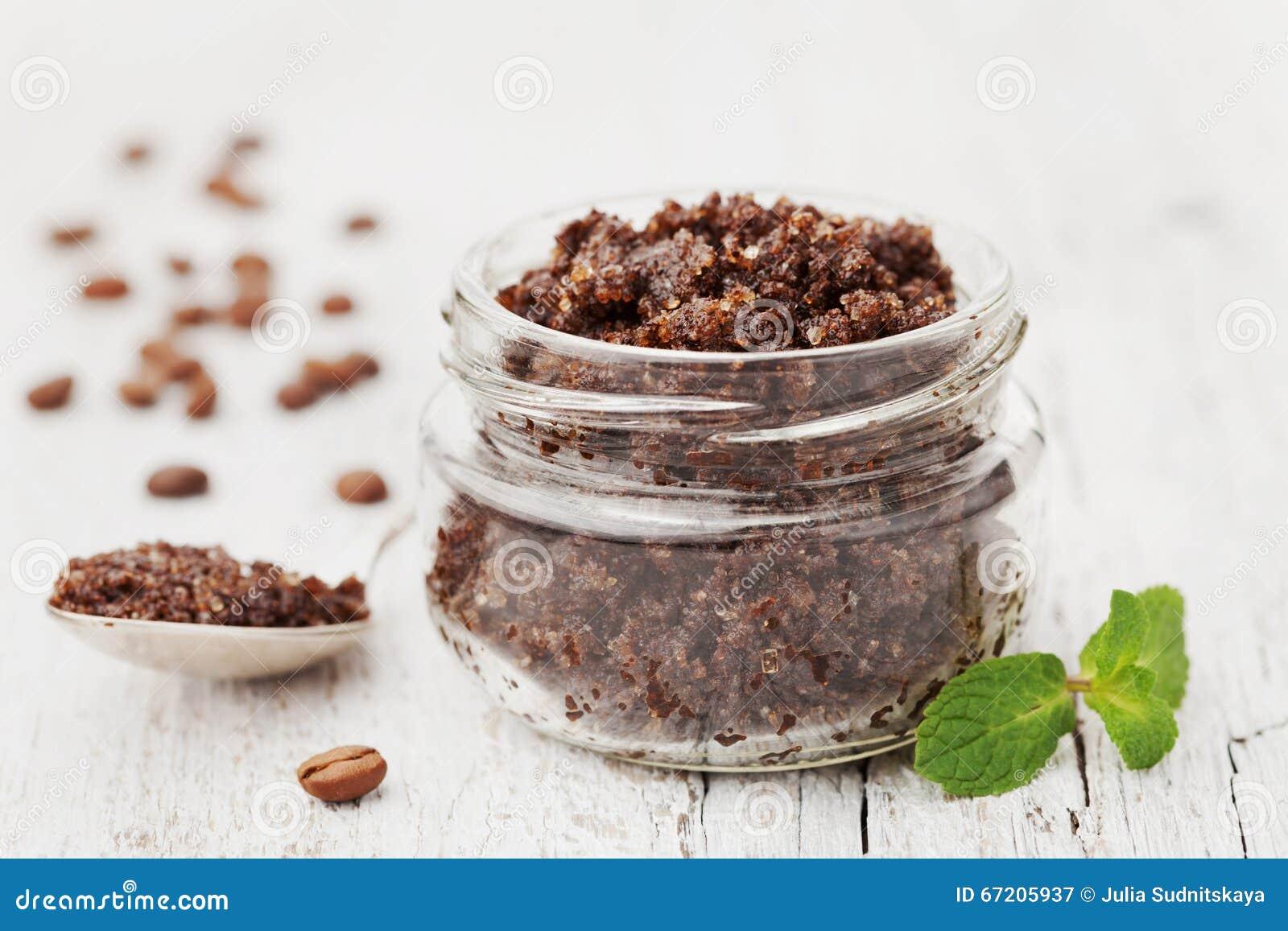 Το σώμα τρίβει του επίγειου καφέ, της ζάχαρης και του ελαίου καρύδων στο βάζο γυαλιού στον άσπρο αγροτικό πίνακα, του σπιτικού κα