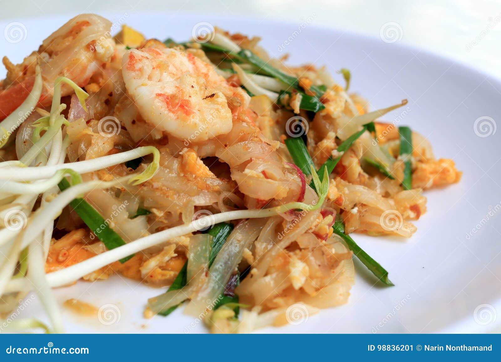 Το ταϊλανδικό μαξιλάρι Ταϊλανδός τροφίμων, ανακατώνει τα νουντλς τηγανητών με τις γαρίδες στο άσπρο πιάτο Ένα από το εθνικό κύριο