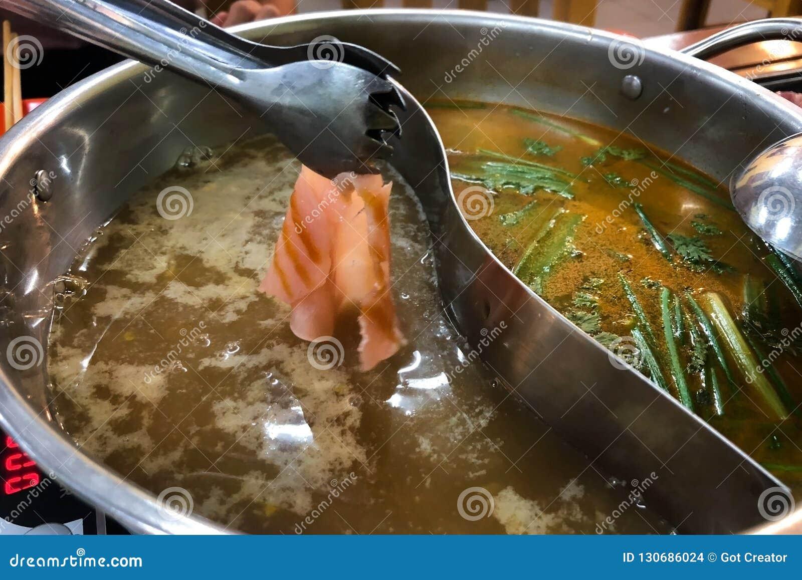 Το τεμαχισμένο κρέας βυθίζεται στην καυτή βράζοντας μαύρη σούπα στο κατάστημα shabu