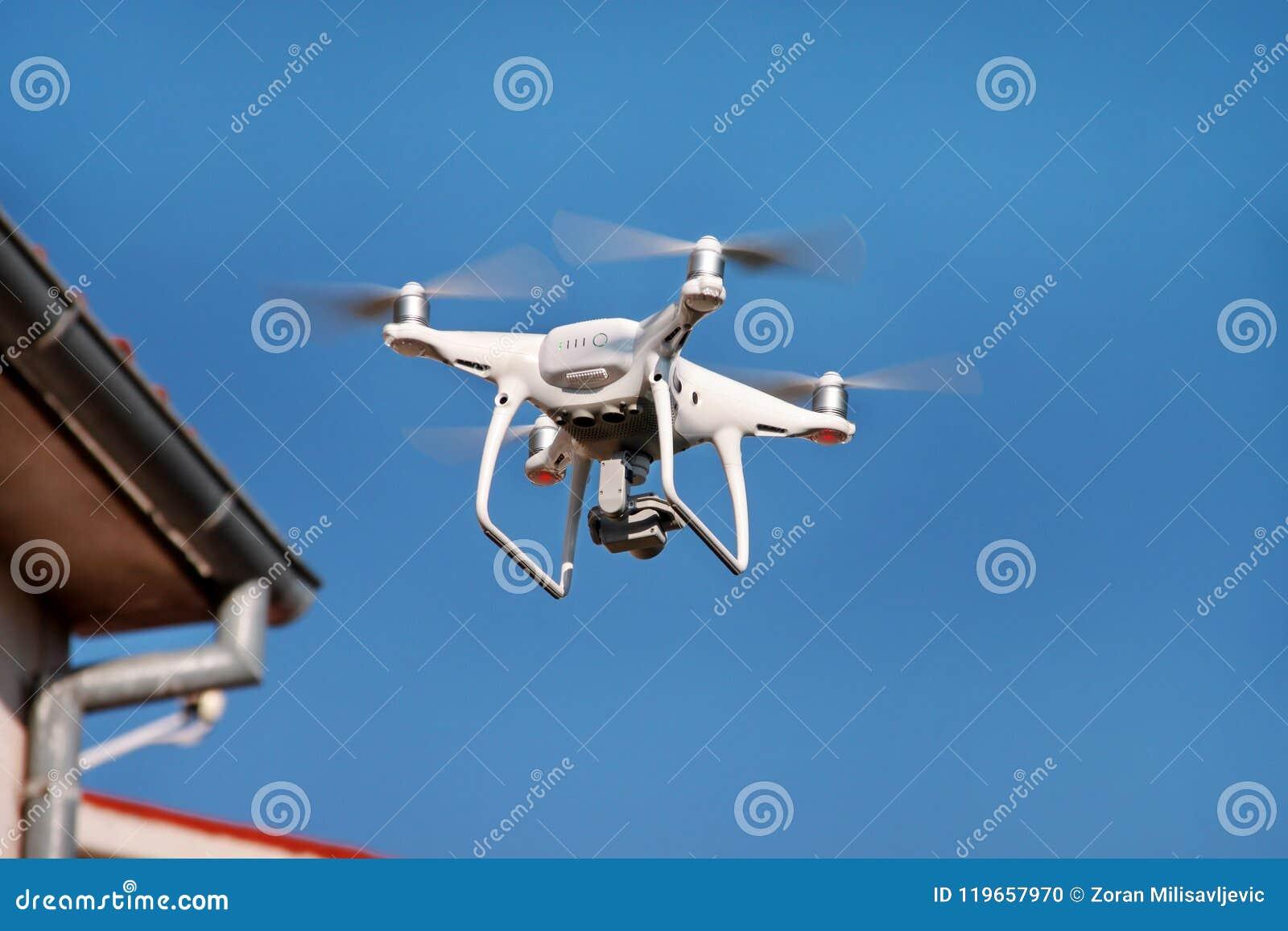 Το τετράγωνο κηφήνων copter πετά στο μπλε ουρανό στο υπόβαθρο Ο σύγχρονος κηφήνας πετά στον αέρα, για να πάρει τις φωτογραφίες κα