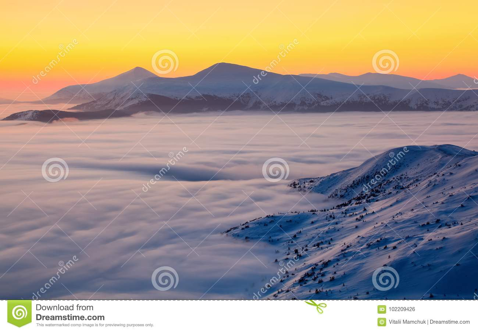 Το τοπίο ένα ζαλίζοντας ηλιοβασίλεμα, μια ενδιαφέροντα παχιά ομίχλη και βουνά που καλύπτονται με με το κατασκευασμένο χιόνι μια χ