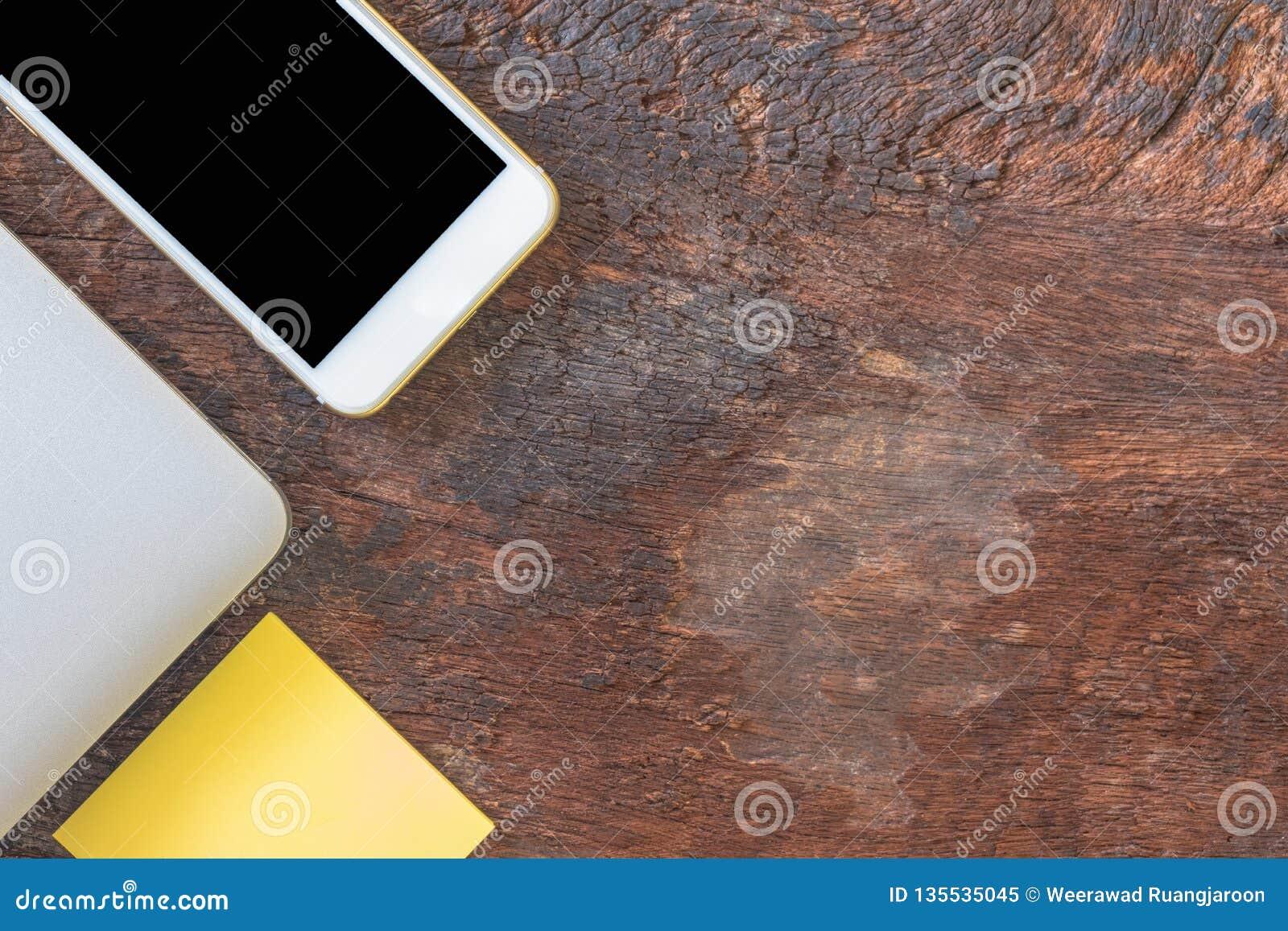 Το τοπ smartphone άποψης, το lap-top, και η μετα σημείωση ή το ταχυδρομούν στο παλαιό ξύλινο υπόβαθρο