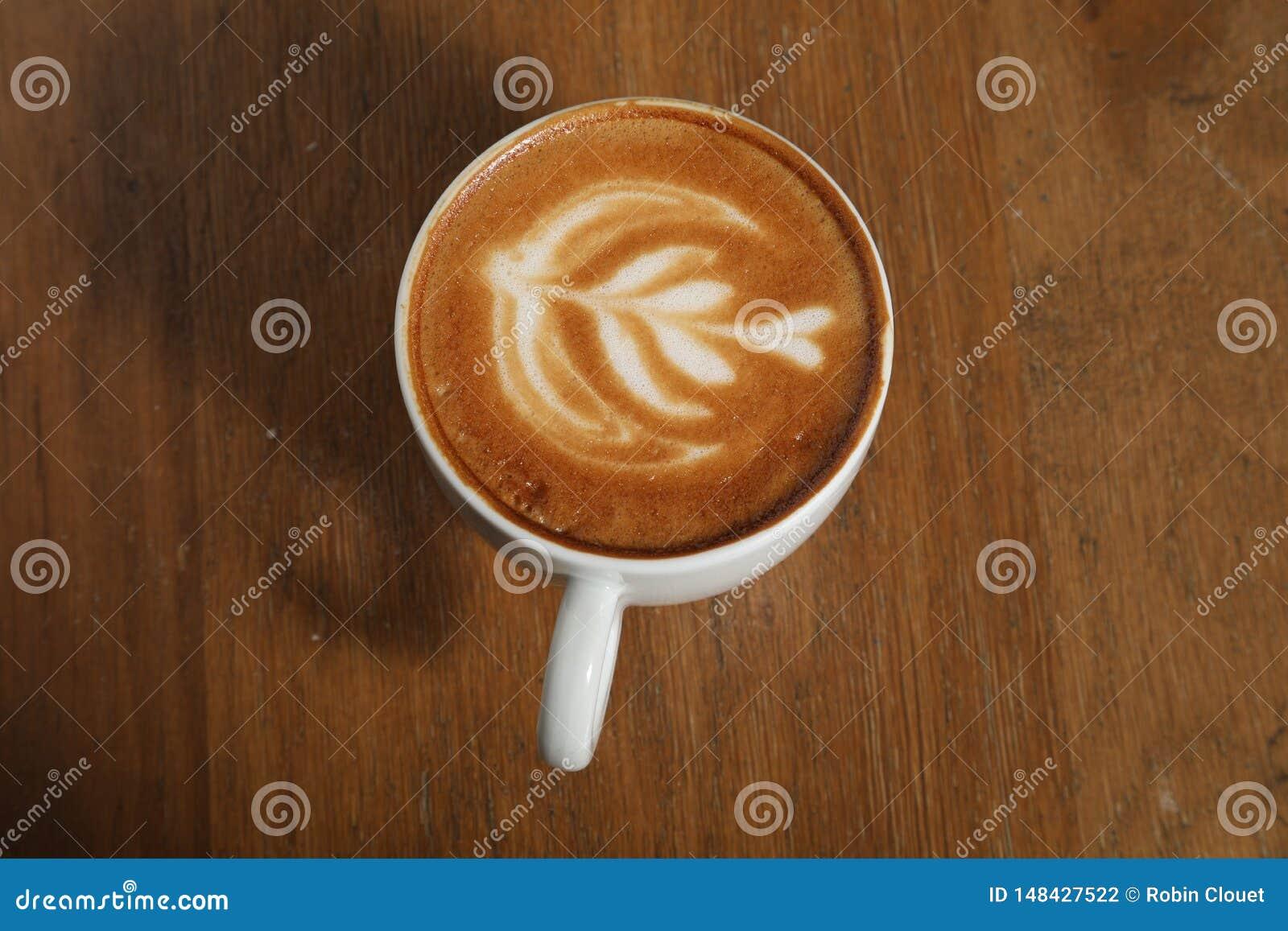 Το φλιτζάνι του καφέ συμπαθητικό σύρει στην κρέμα