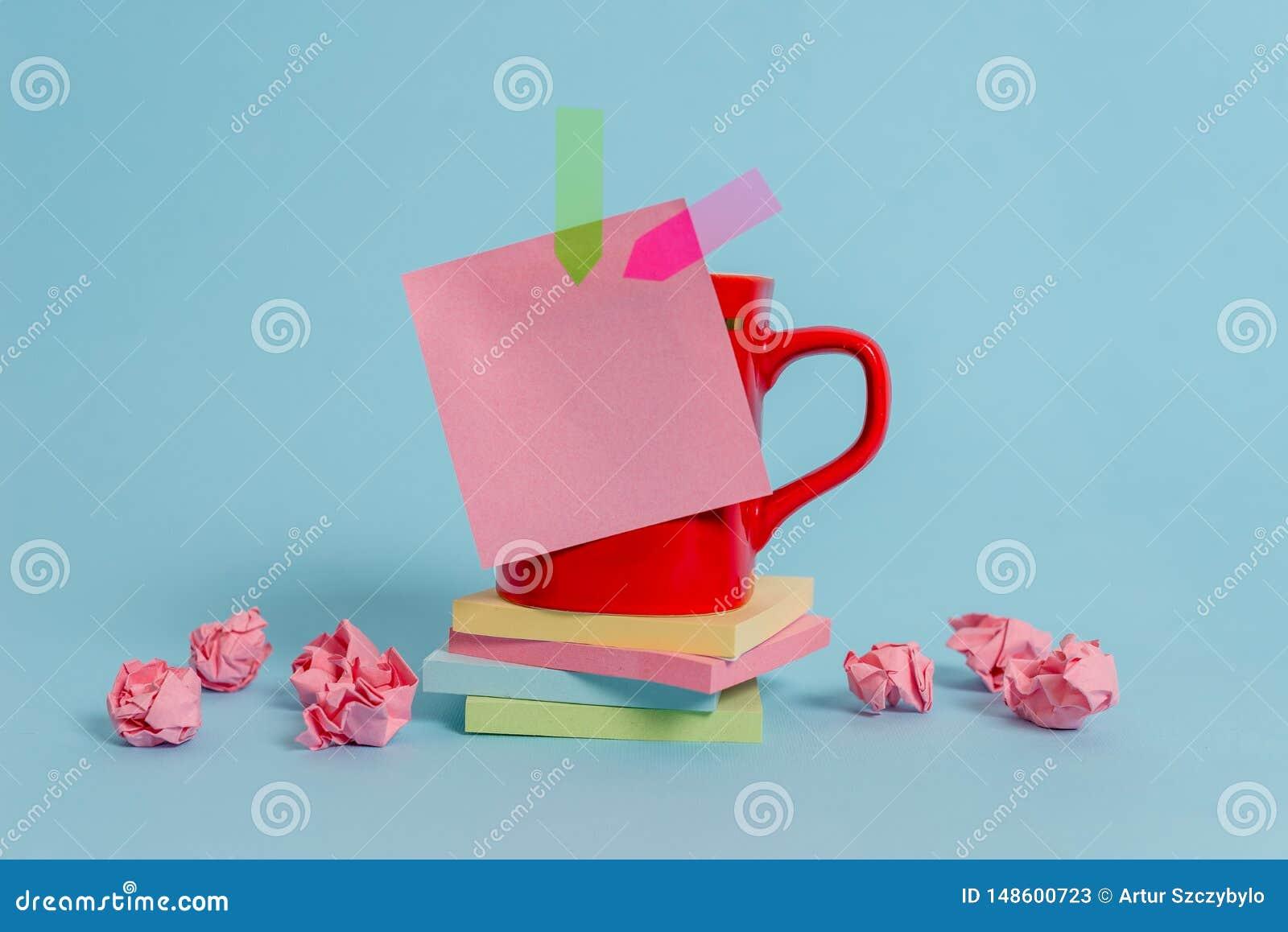 Το φλυτζάνι καφέ μπροστινής άποψης χρωμάτισε την κολλώδη να βρεθεί μαξιλαριών εγγράφου βελών σημειώσεων συντριμμένη εμβλήματα συσ