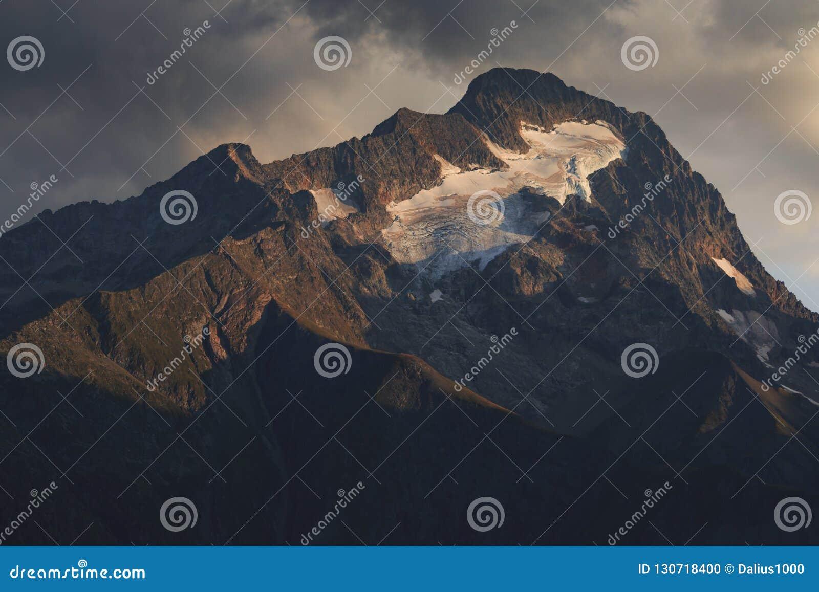 Το φως ηλιοβασιλέματος λάμπει στην αιχμή του βουνού Roche de Λα Muzelle