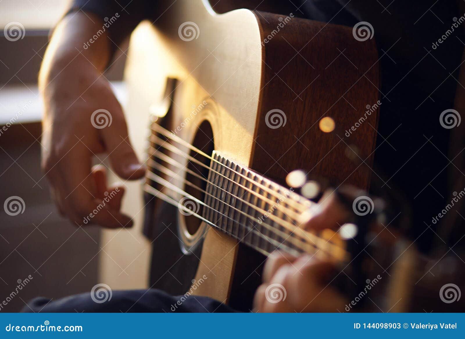 Το φως του ήλιου φωτίζει τον κιθαρίστα, που παίζει μια μελωδία σε μια κιθάρα