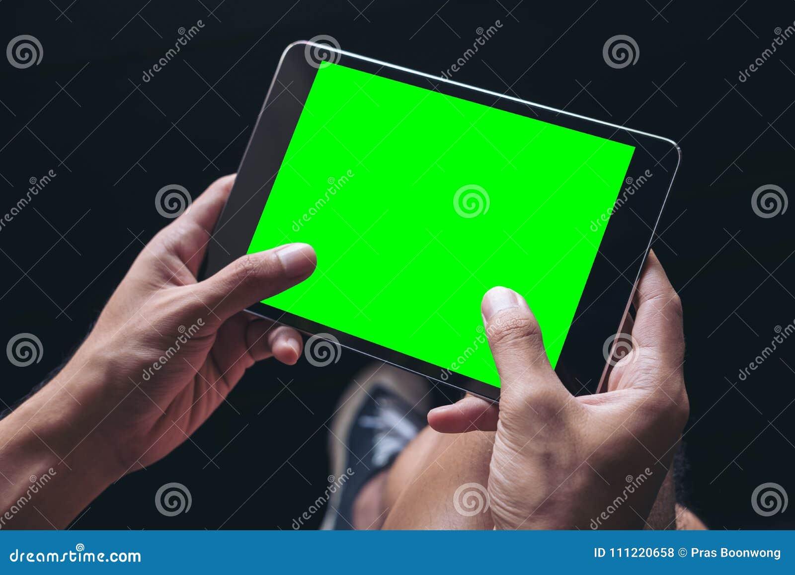 Το χέρια ατόμων ` s που κρατούν το μαύρο PC ταμπλετών με την κενή πράσινη οθόνη στο μηρό στο μαύρο υπόβαθρο