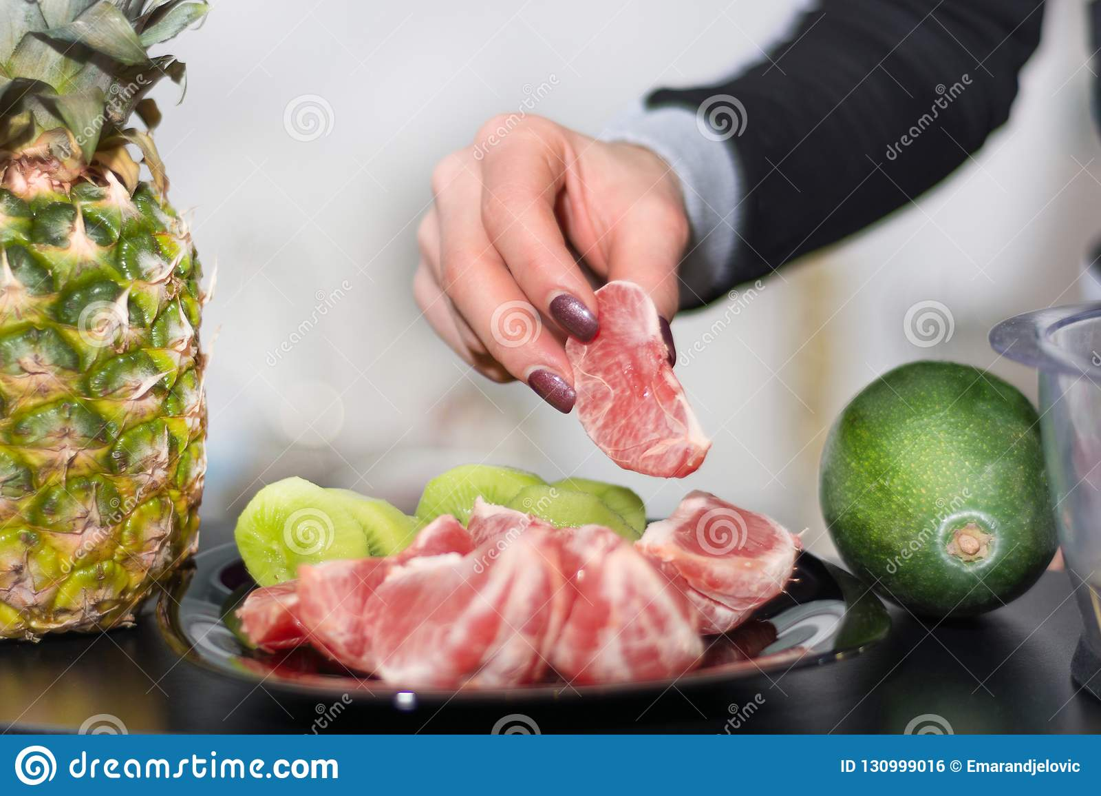 Το χέρι γυναικών κρατά το κόκκινο ξεφλουδισμένο γκρέιπφρουτ στο πιάτο