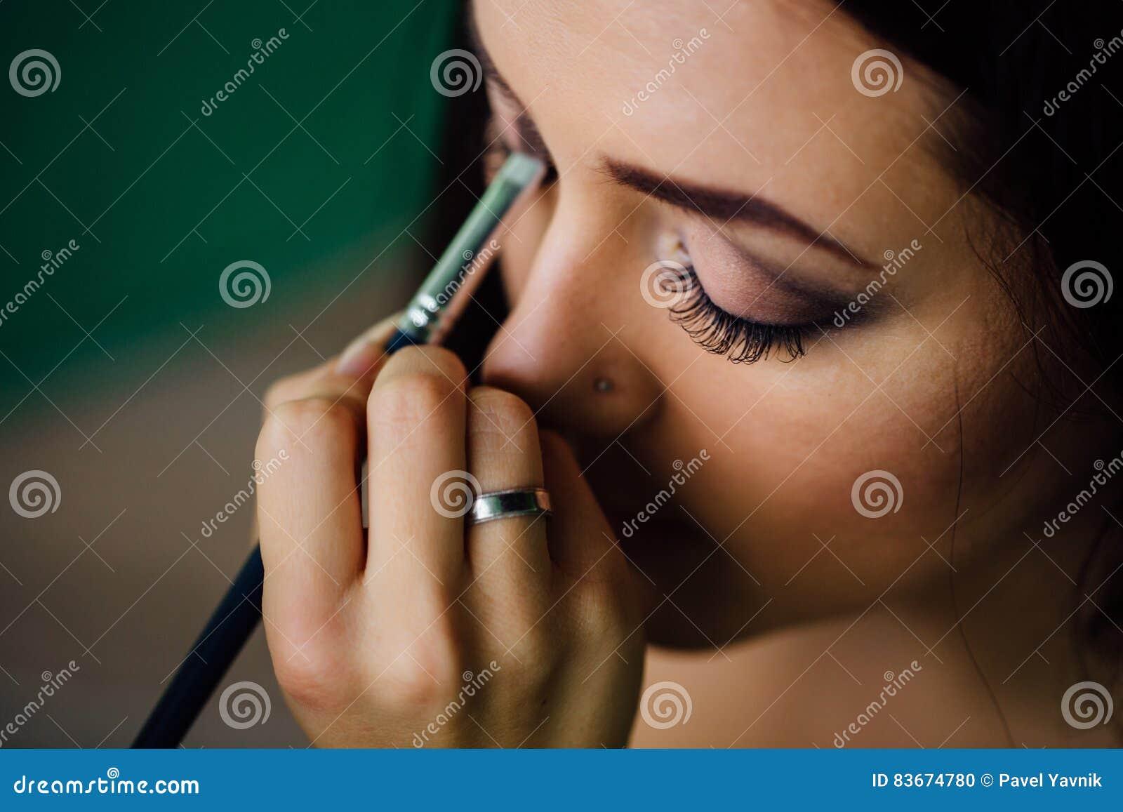 Το χέρι καλλιτεχνών σύνθεσης που εφαρμόζει το φωτεινό χρώμα βάσεων στο πρότυπο πρόσωπο ` s και που κρατά μια βούρτσα, κλείνει