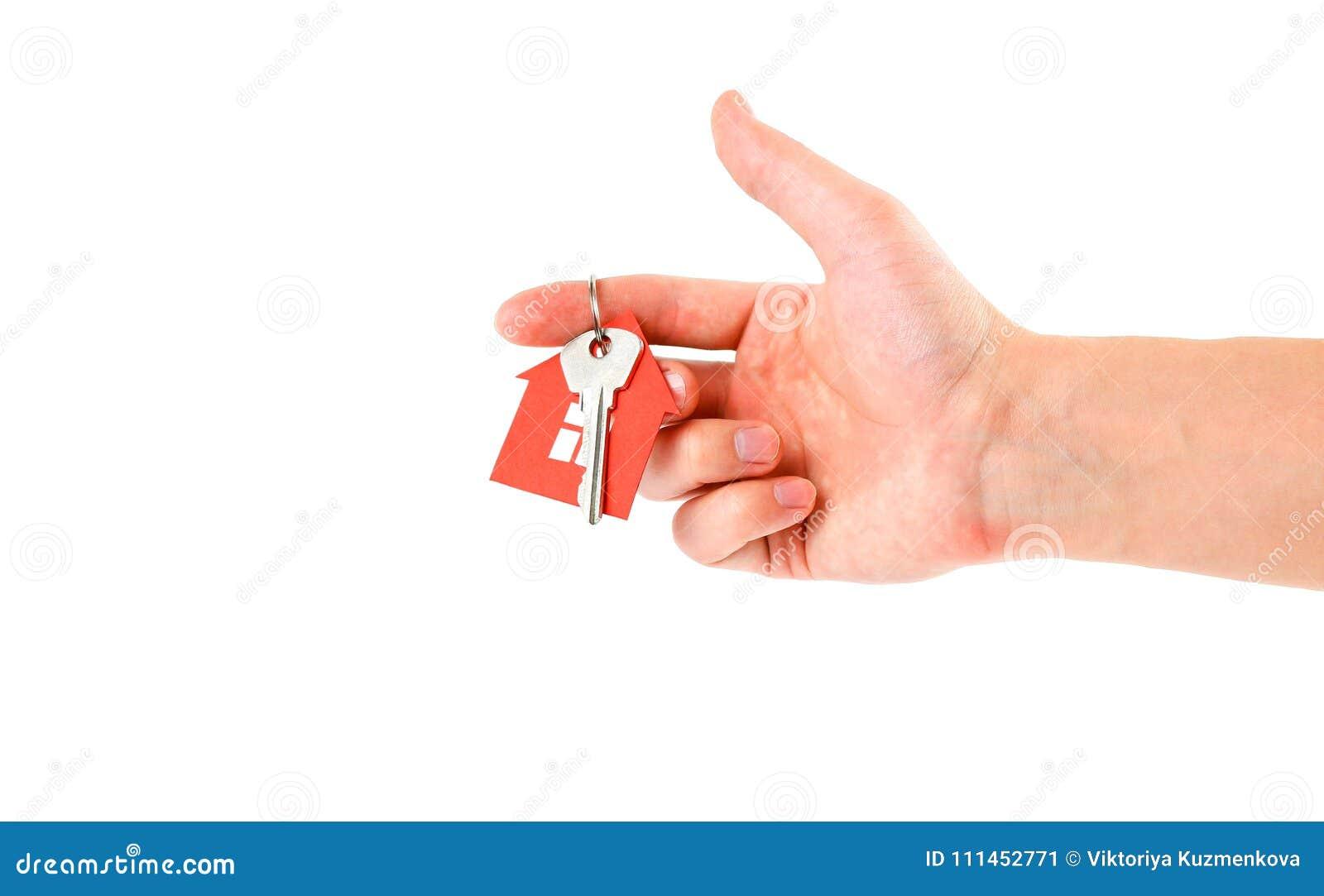 Το χέρι κρατά τα κλειδιά με το κόκκινο σπίτι keychain Αγορά
