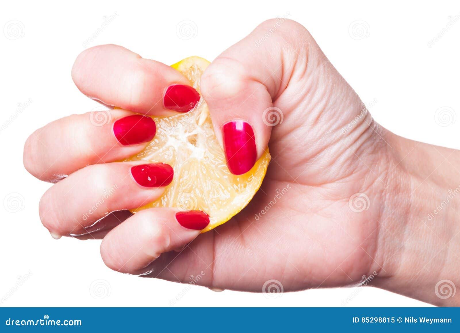 Το χέρι με το λεμόνι συμπιέσεων καρφιών στο λευκό