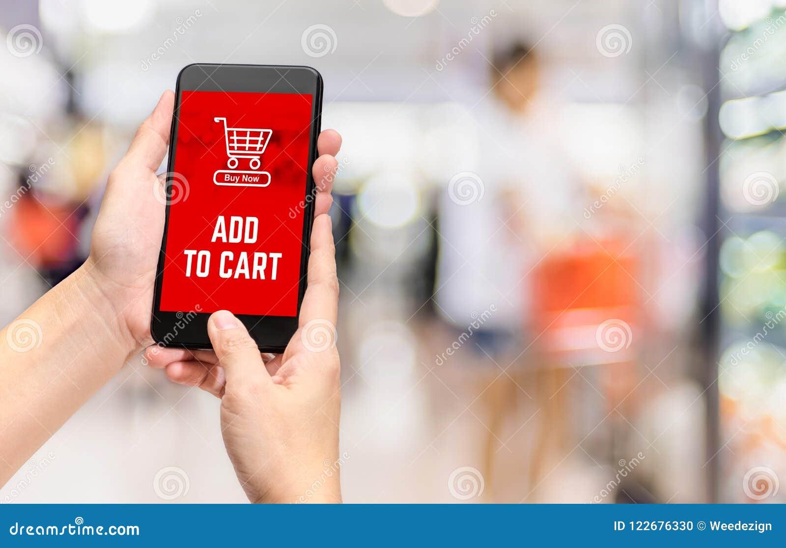 Το χέρι που κρατά κινητό προσθέτει στο προϊόν κάρρων στην αγορά σε απευθείας σύνδεση με