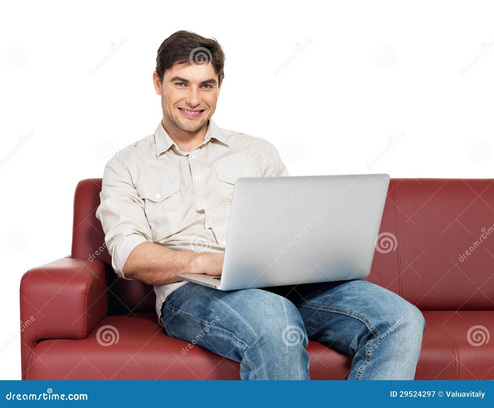 Το χαμογελώντας ευτυχές άτομο με το lap-top κάθεται στο ντιβάνι