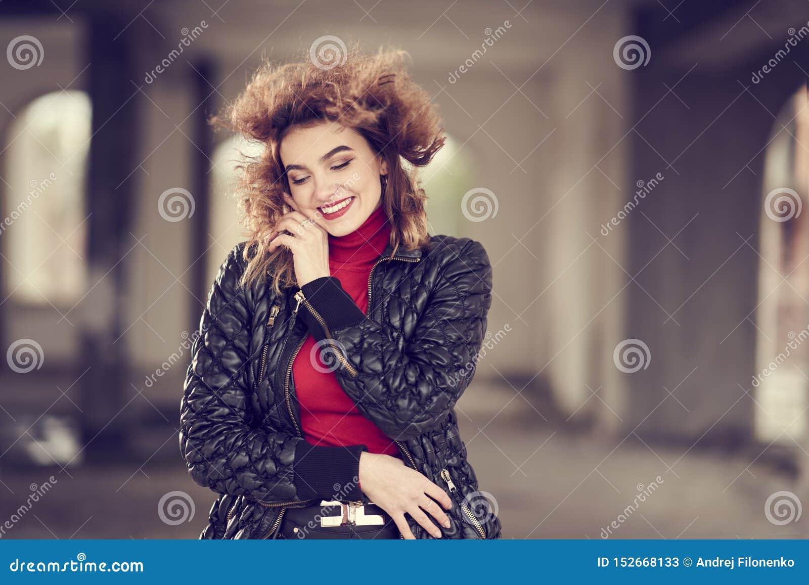 Το χαμογελώντας μοντέρνο κοκκινομάλλες κορίτσι με τη ρέοντας τρίχα στο μαύρο δέρμα ασθμαίνει, κόκκινο πουλόβερ και μαύρη τοποθέτη