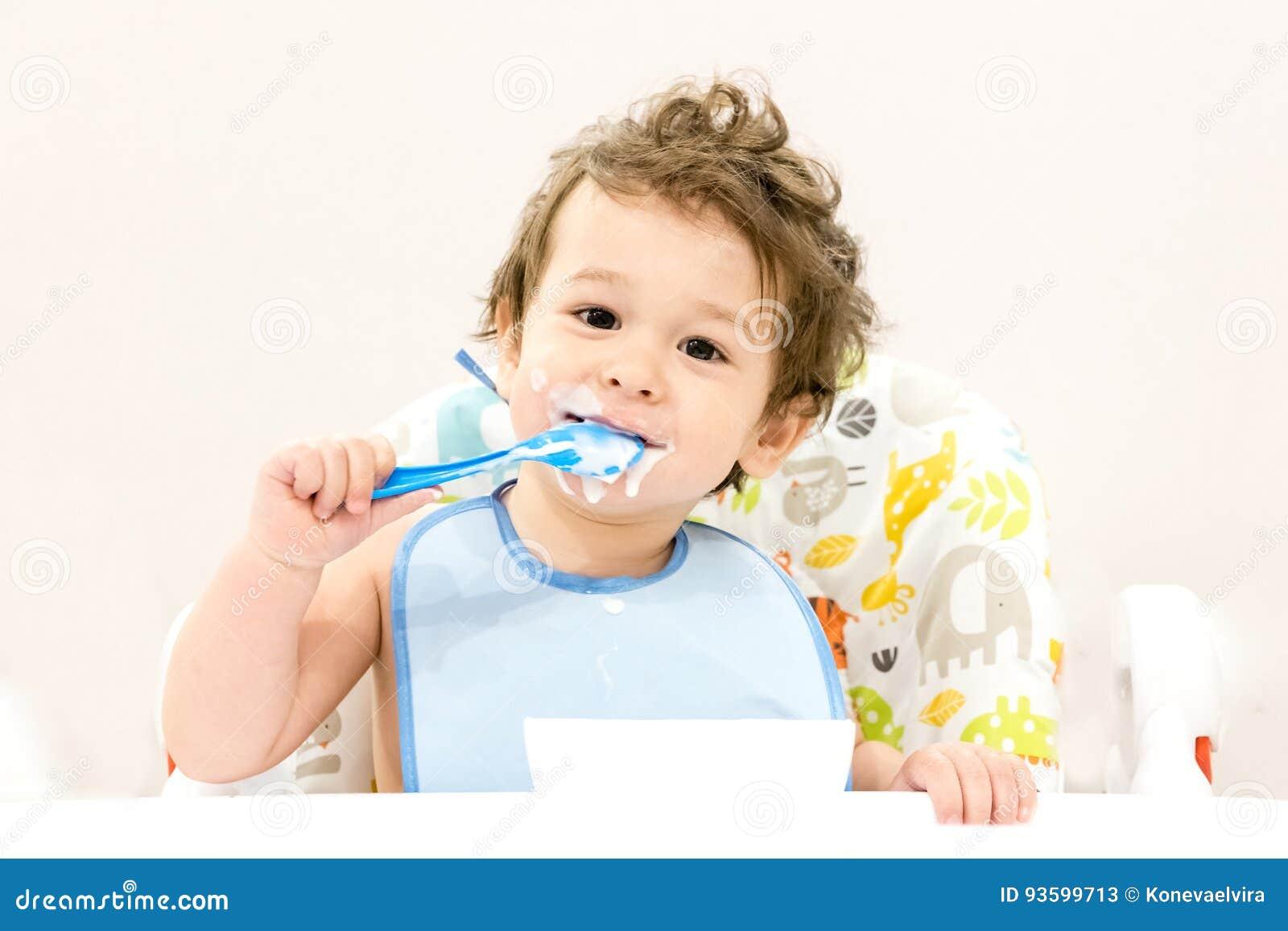 Το χαριτωμένο αγόρι μικρών παιδιών με το μπλε κουτάλι είναι γιαούρτι Τα χαμόγελα παιδιών αστείο παιδί σε ένα κάθισμα μωρών όμορφο