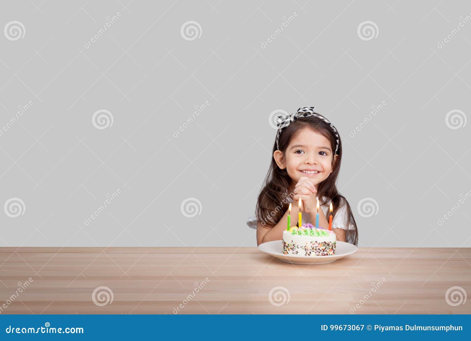 Το χαριτωμένο κορίτσι κάνει μια επιθυμία στα γενέθλια γενέθλια ανασκόπησης ε&upsilon