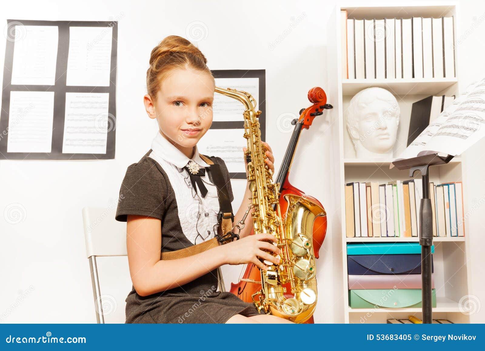 Το χαριτωμένο κορίτσι στο φόρεμα σχολικών στολών κρατά το saxophone