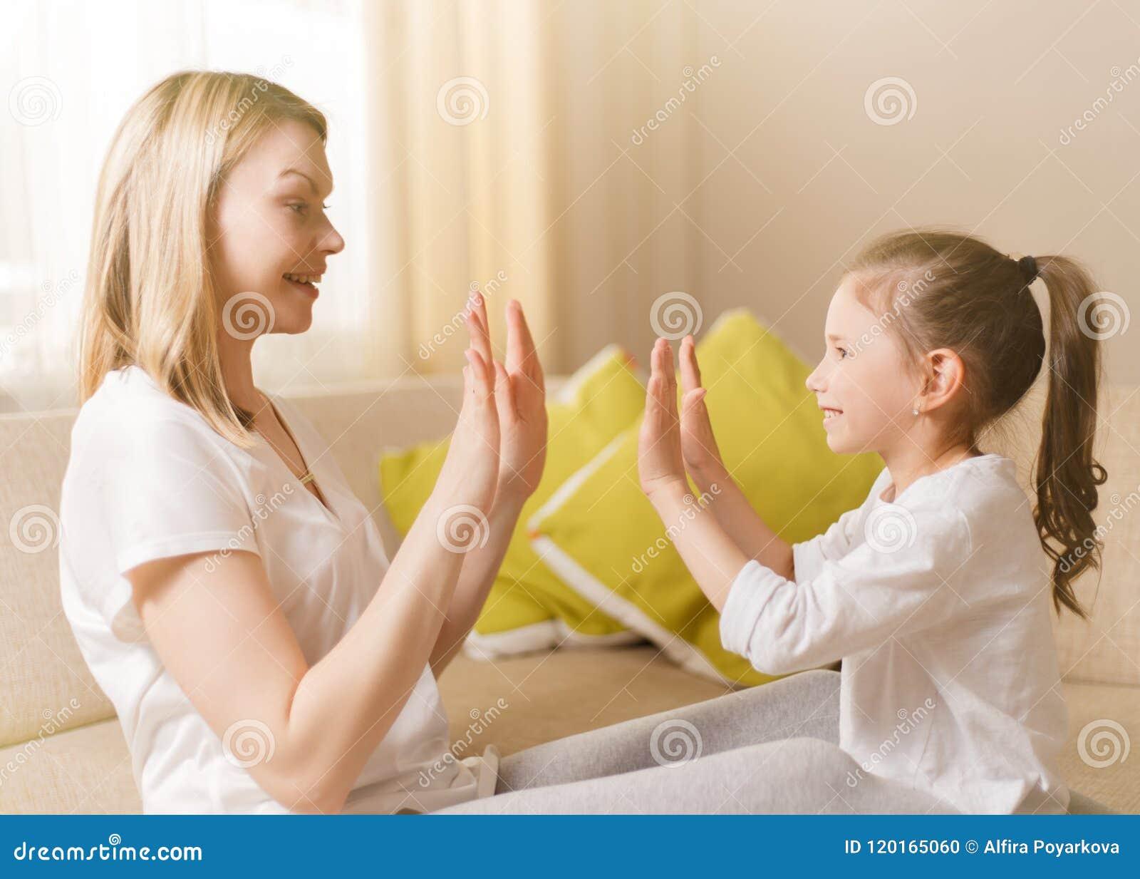 Το χαριτωμένο μικρό κορίτσι και η όμορφη μητέρα της είναι παίζοντας παιχνίδια στο σπίτι, χτυπώντας τα χέρια από κοινού