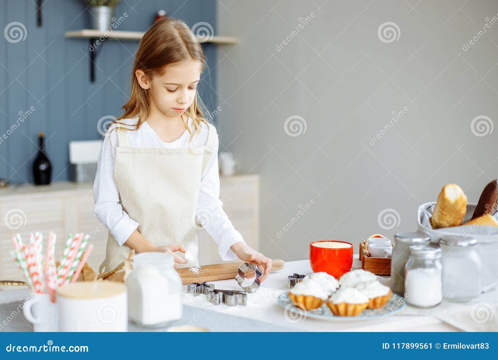 Το χαριτωμένο μικρό κορίτσι στην ποδιά μαγειρεύει τα μπισκότα στην κουζίνα