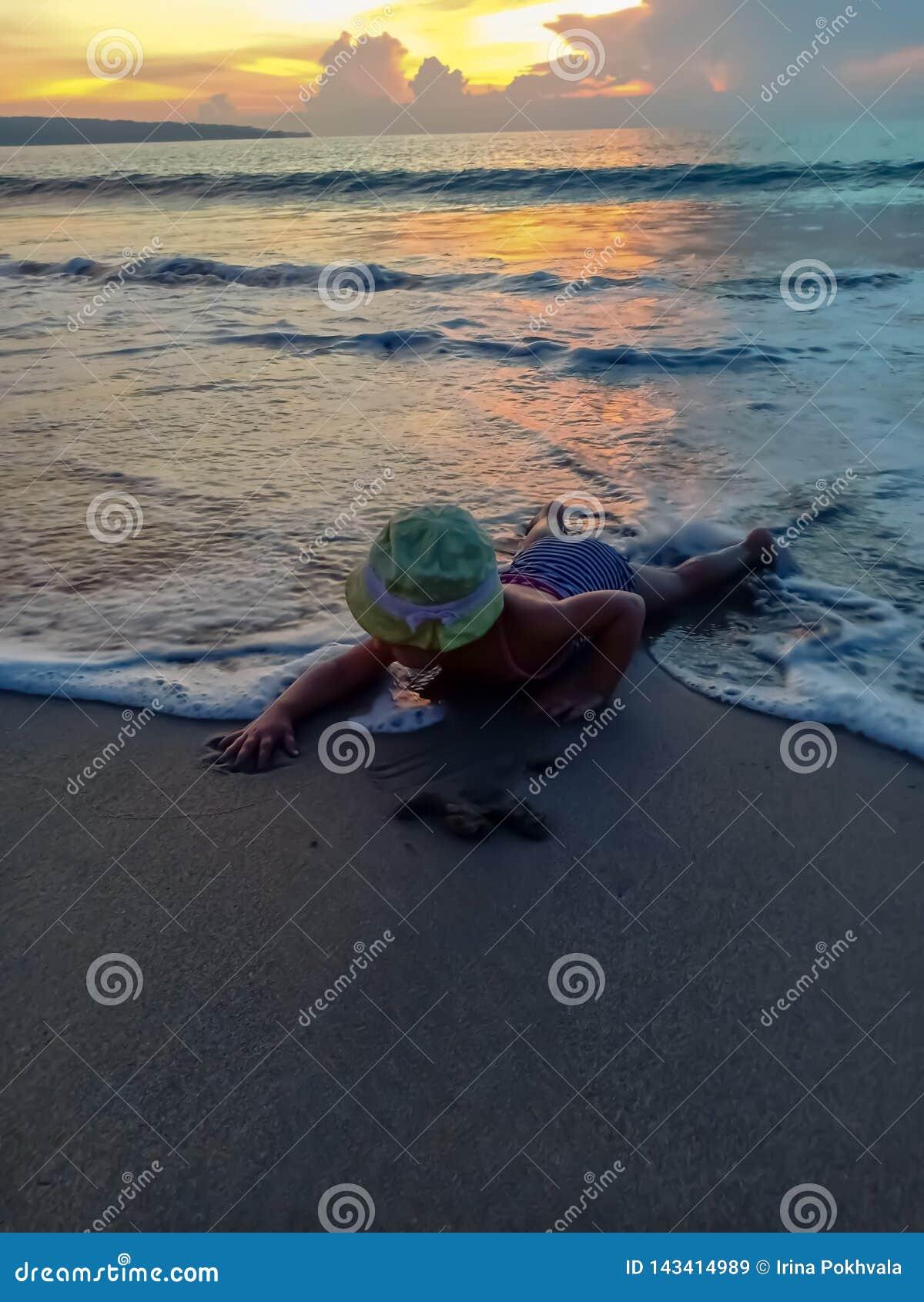 Το χαριτωμένο μικρό κορίτσι συναντά το ηλιοβασίλεμα και κατοχή της διασκέδασης στην παραλία