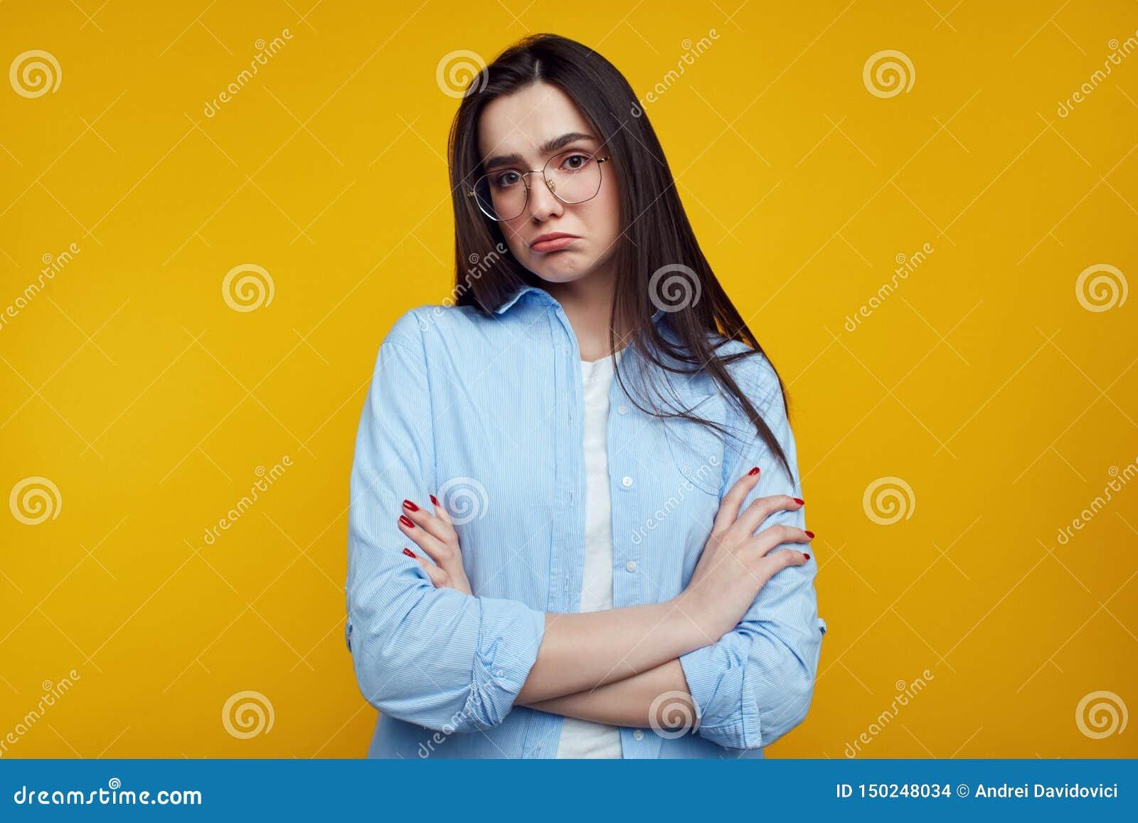 Το χαριτωμένο νέο κορίτσι έχει ανατρέψει κοιτάζει, καμπύλες που το χαμηλότερο χείλι, εκφράζει το dissatifaction και τη δυσαρέσκει