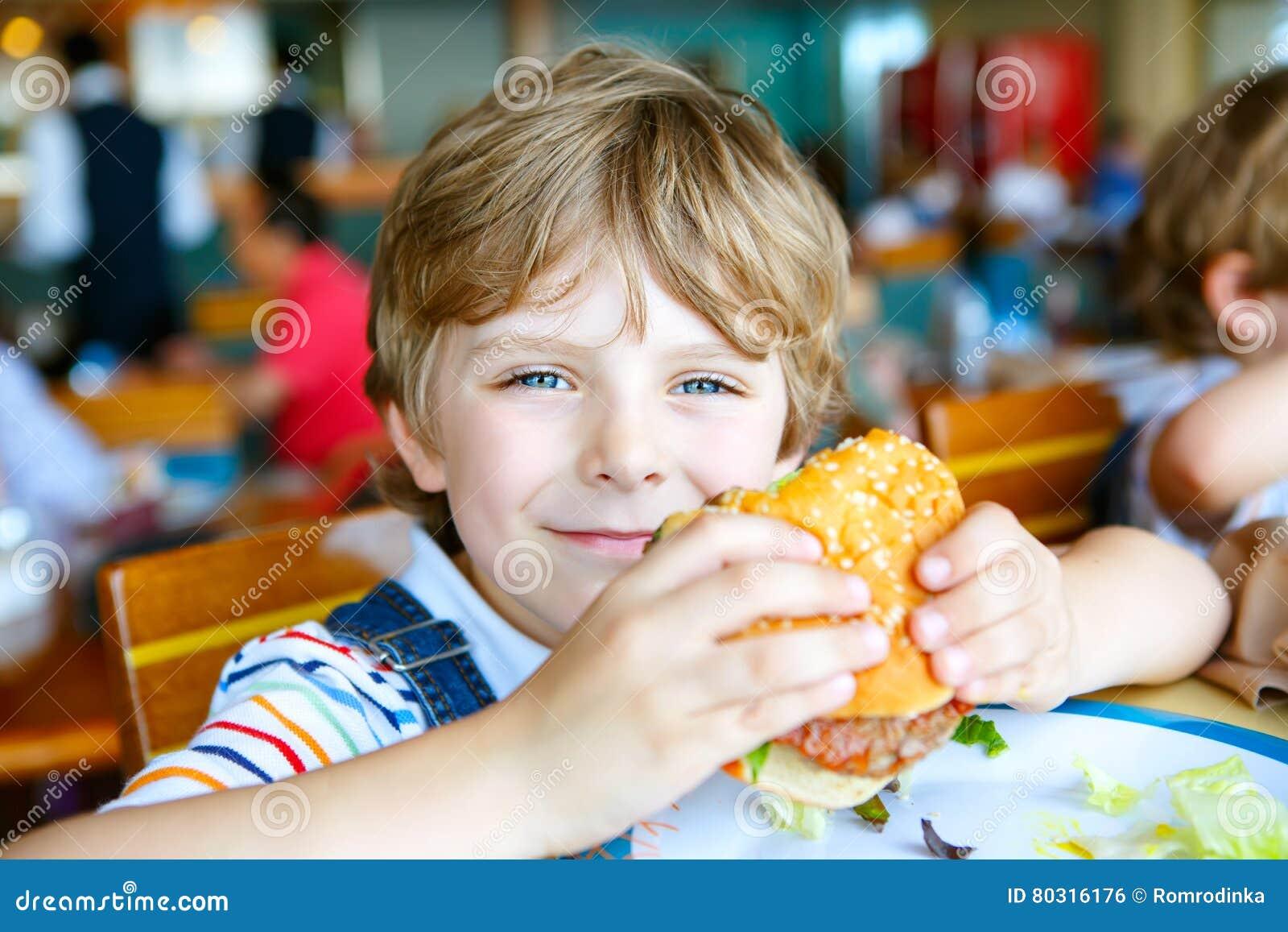 Το χαριτωμένο υγιές προσχολικό αγόρι τρώει τη συνεδρίαση χάμπουργκερ στον καφέ υπαίθρια