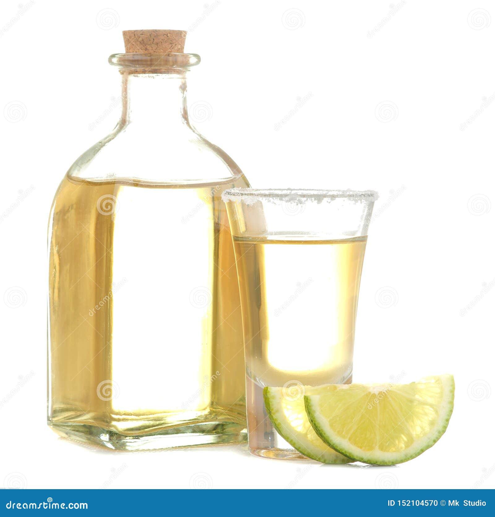 Το χρυσό tequila σε ένα γυαλί με το άλας και ο ασβέστης σε ένα λευκό απομόνωσαν το υπόβαθρο οινοπνευματώδη ποτά E