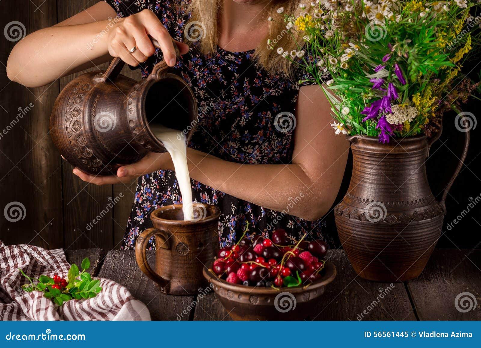 Download Το χύνοντας γάλα κοριτσιών από μια κανάτα σε ένα φλυτζάνι και ένα κύπελλο με τα μούρα σε έναν ξύλινο πίνακα κανάτα λουλουδιών Στοκ Εικόνα - εικόνα από εύθυμος, αγροτικός: 56561445