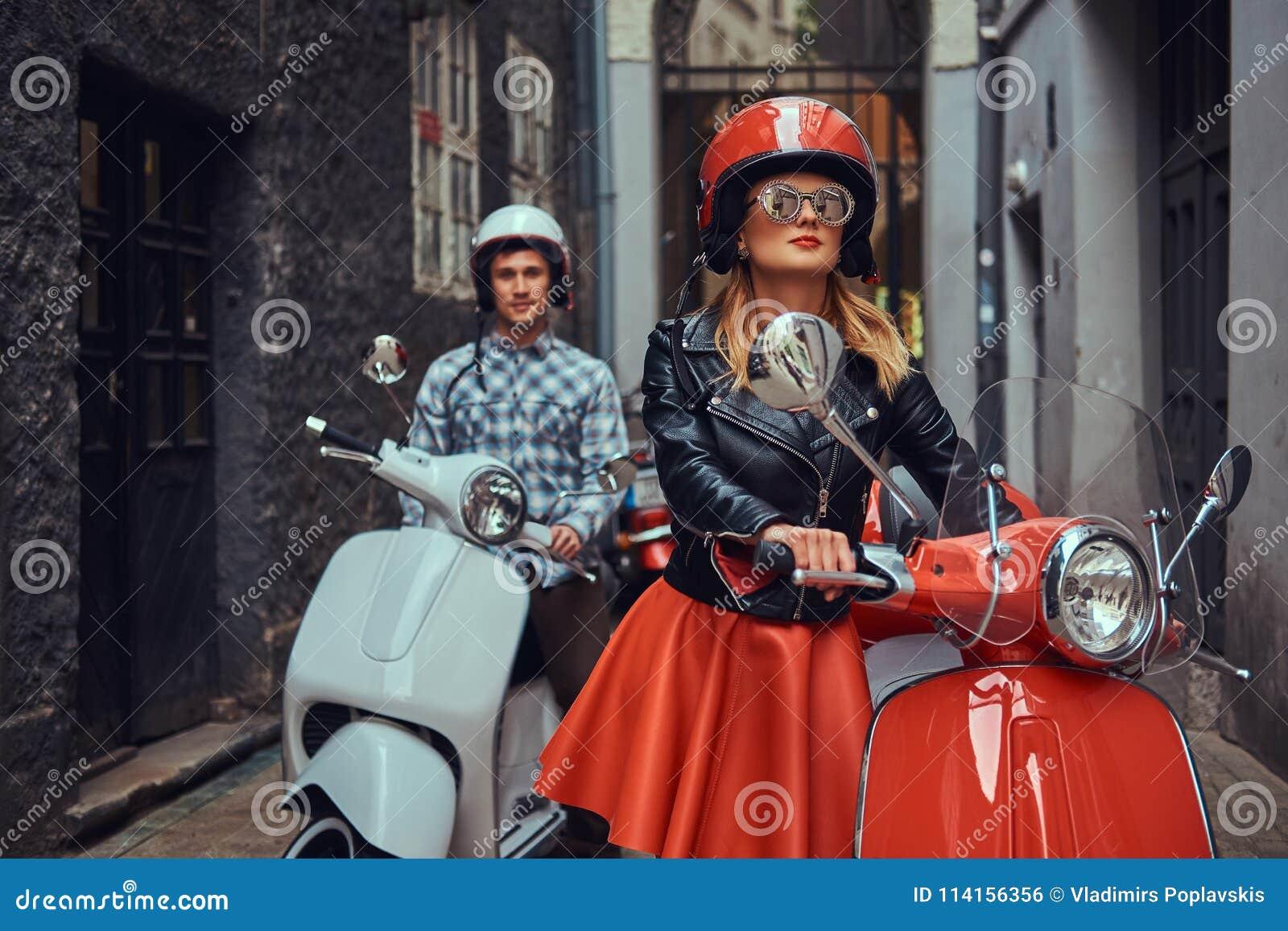 Το όμορφο άτομο και ένα προκλητικό μοντέρνο κορίτσι περπατούν με τα αναδρομικά ιταλικά μηχανικά δίκυκλα κατά μήκος των παλαιών οδ