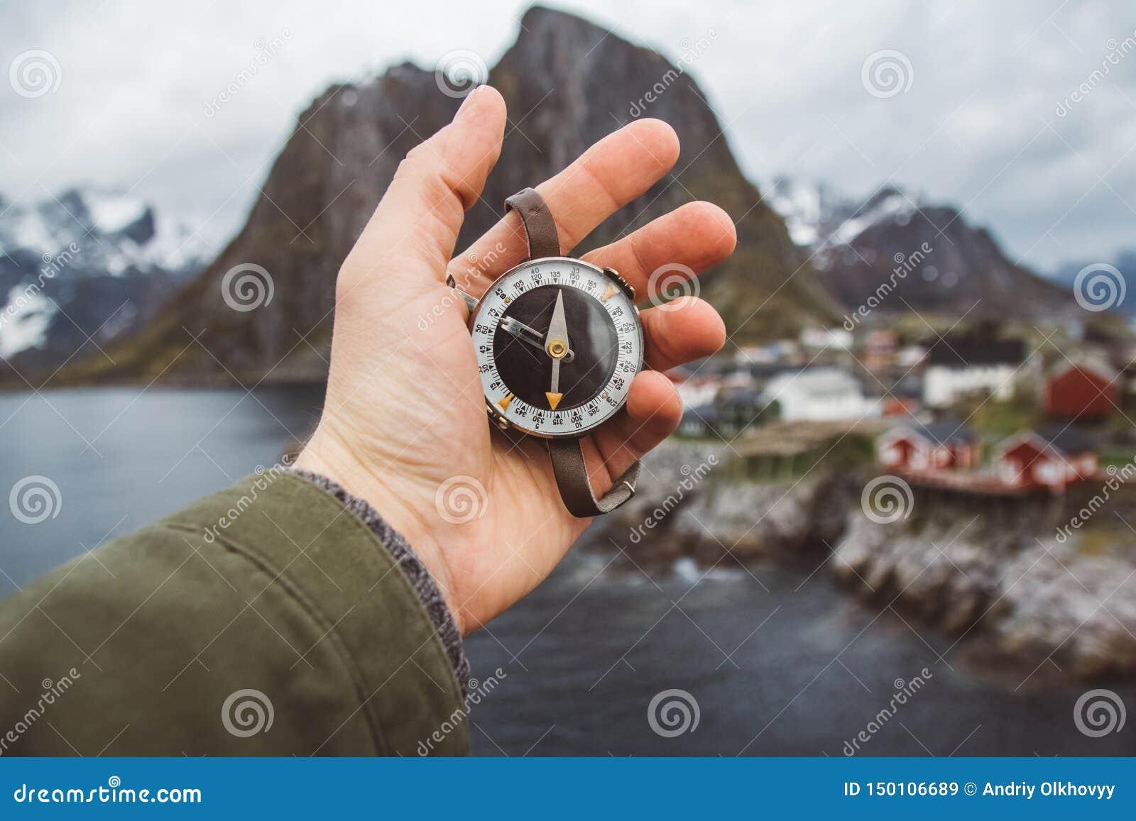 Το όμορφο αρσενικό χέρι κρατά μια μαγνητική πυξίδα στα πλαίσια των σπιτιών και των βράχων βουνών πέρα από το φιορδ