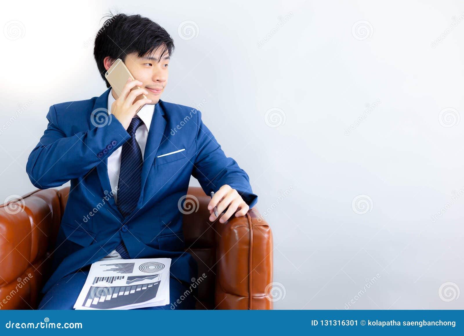 Το όμορφο επιχειρησιακό άτομο εξετάζει το διάστημα αντιγράφων κατά τη διάρκεια της χρησιμοποίησης του τηλεφώνου για