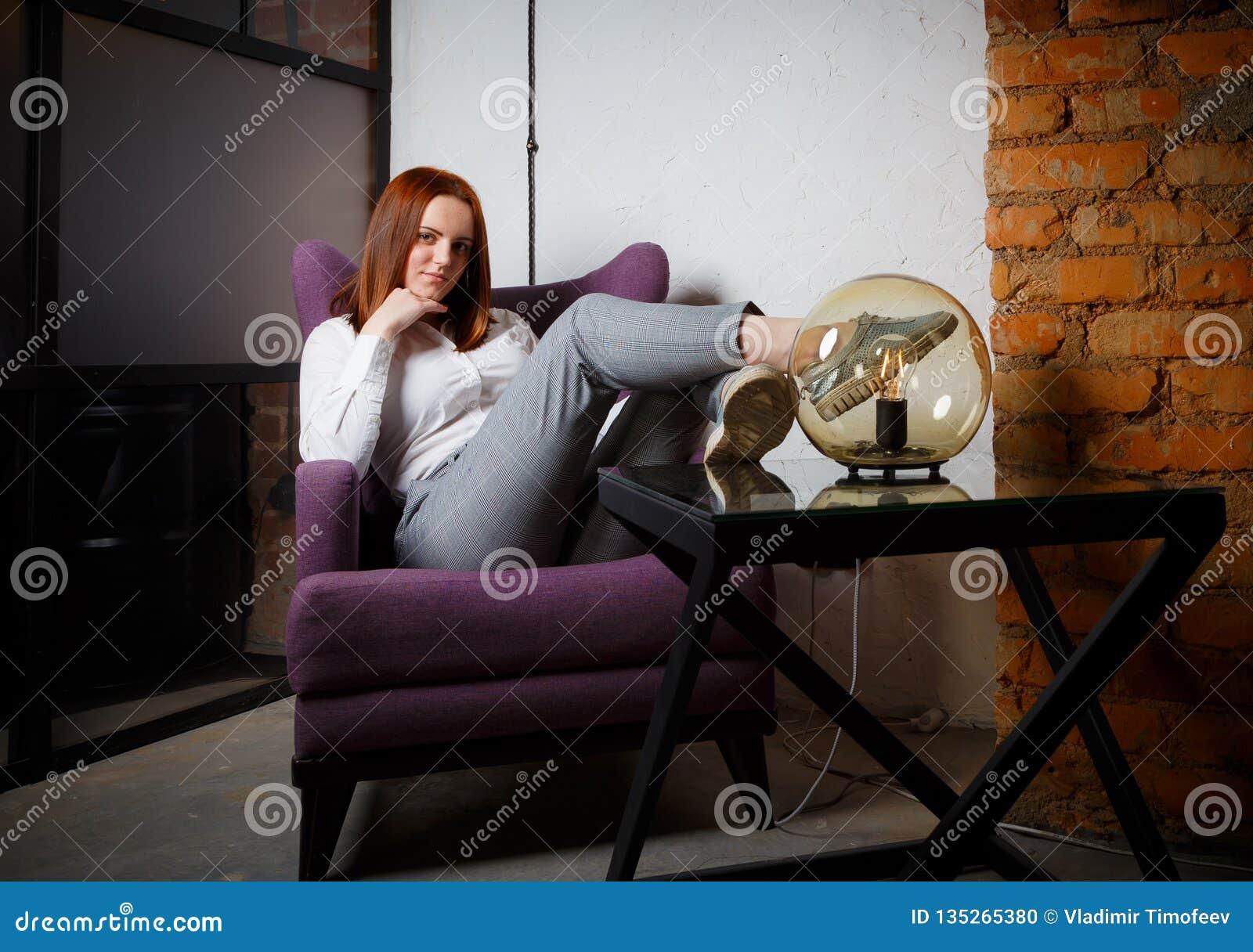 Το όμορφο καθαρισμένο κορίτσι με τη μακροχρόνια κόκκινη συνεδρίαση τρίχας χαλάρωσε στην καφετιά καρέκλα δέρματος Φωτεινοί θερμοί