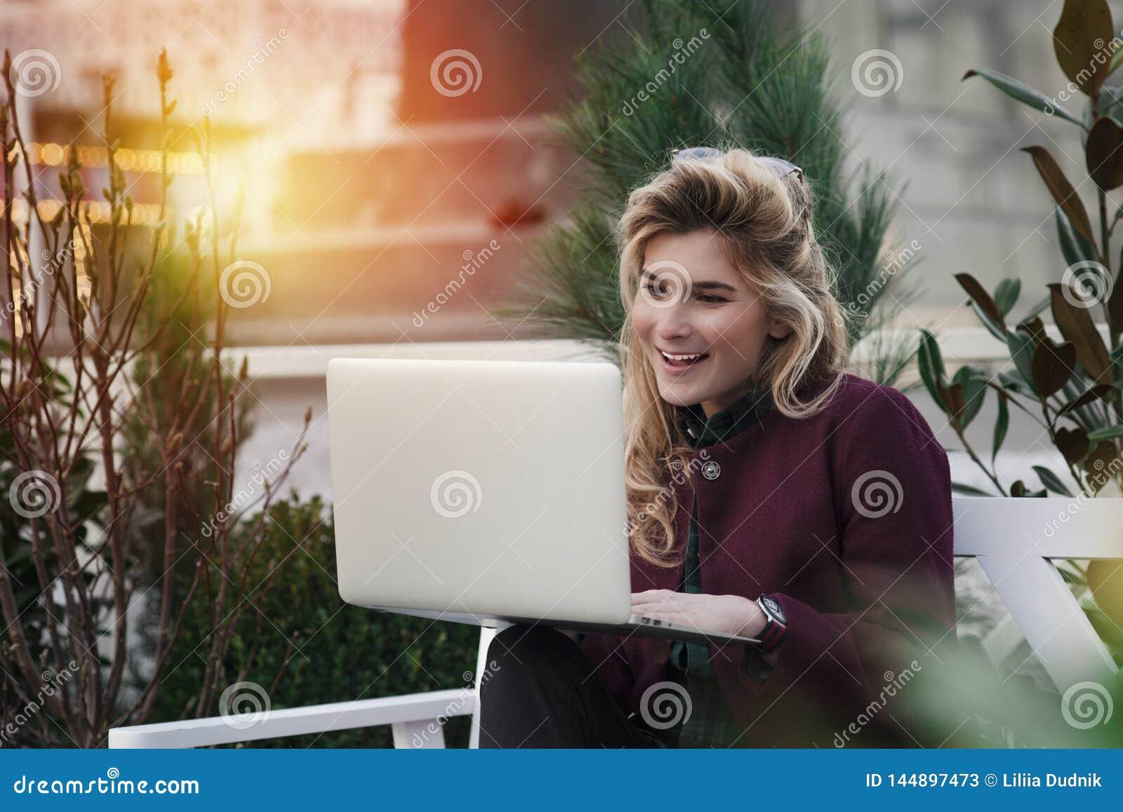 Το όμορφο κορίτσι κάθεται σε έναν πάγκο με ένα lap-top στα χέρια της σε μια