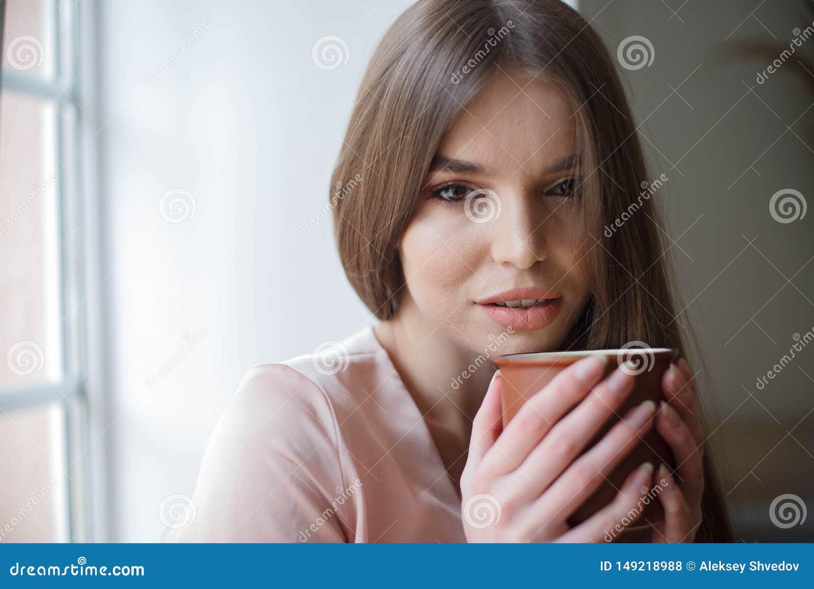 Το όμορφο κορίτσι πίνει τον καφέ και χαμογελά καθμένος στον καφέ