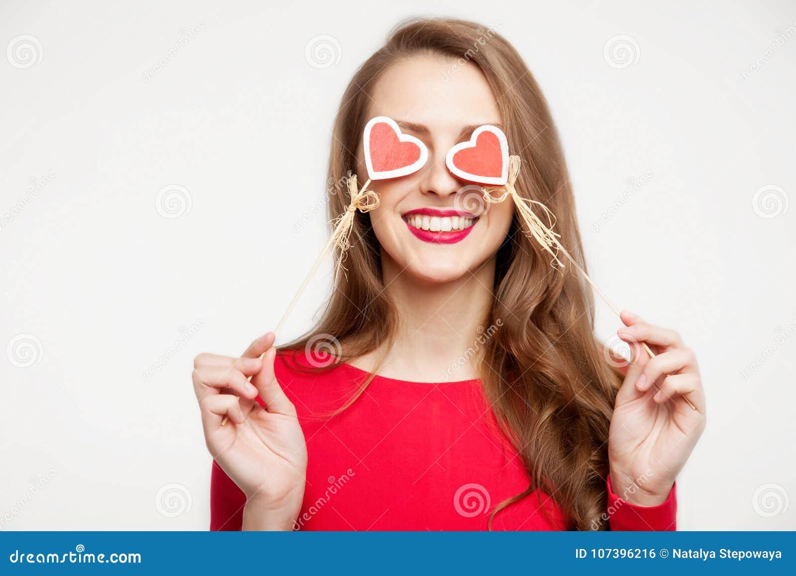 Το όμορφο κορίτσι brunette έκλεισε τα μάτια της με δύο καρδιές των αναμνηστικών Έννοια ημέρας βαλεντίνων ` s Στην άσπρη ανασκόπησ