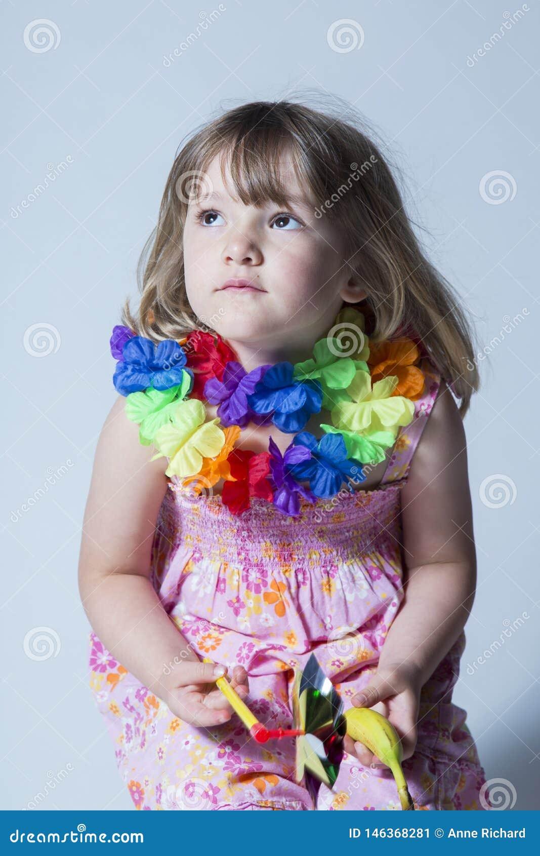 Το όμορφο μικρό κορίτσι έντυσε στη ρόδινη floral συνεδρίαση γιρλαντών λουλουδιών φορεμάτων και μεταξιού στο σκαμνί