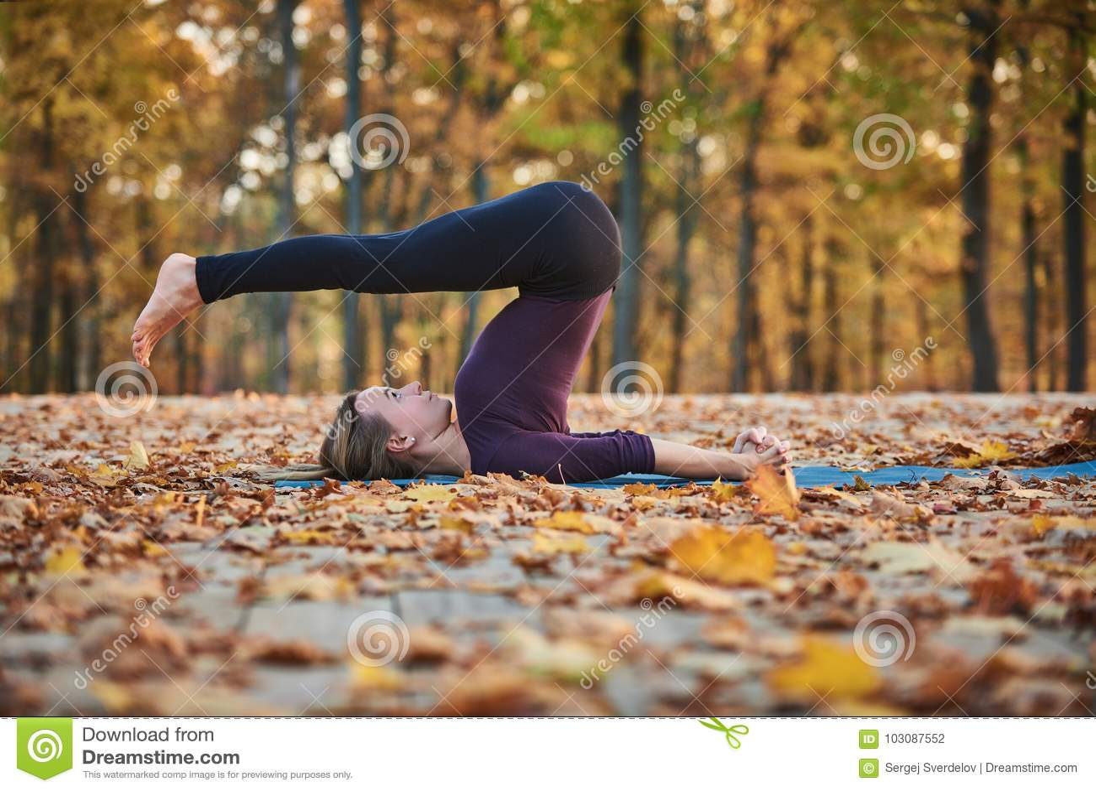 Το όμορφο νέο άροτρο Halasana asana γιόγκας πρακτικών γυναικών θέτει στην ξύλινη γέφυρα στο πάρκο φθινοπώρου
