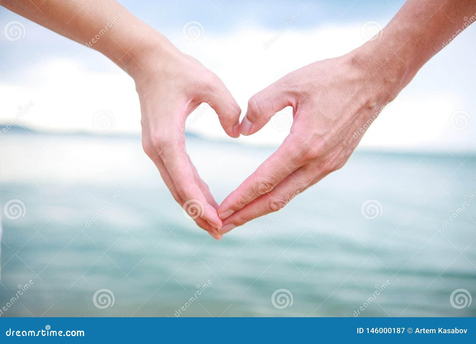 Το όμορφο νέο ζεύγος κάνει την καρδιά με τα δάχτυλα