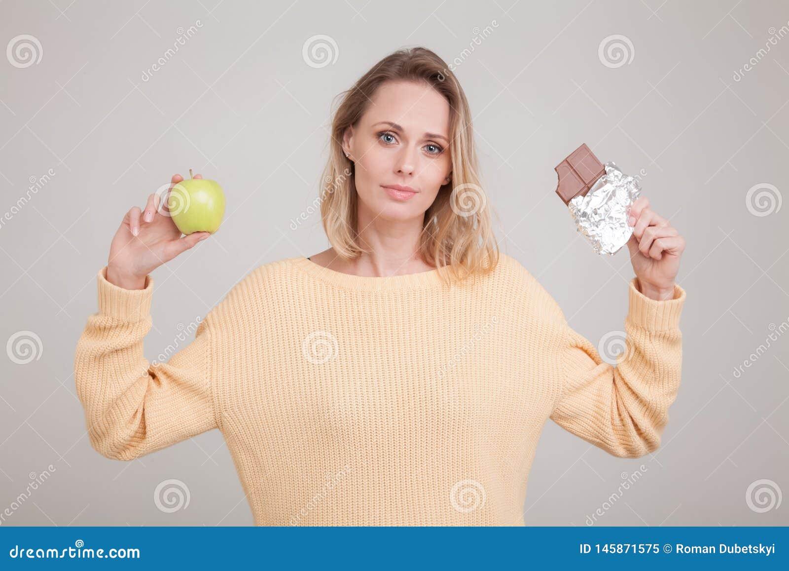Το όμορφο νέο ξανθό κορίτσι κρατά έναν φραγμό της σοκολάτας και ένα πράσινο μήλο γύρω από το πρόσωπό της, δεν μπορεί να κάνει μια