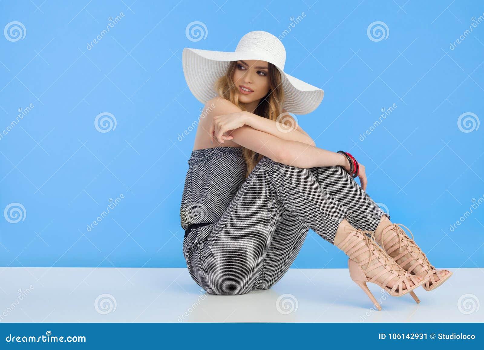 Το όμορφο πρότυπο μόδας σε Jumpsuit και το άσπρο καπέλο ήλιων κάθεται και κοιτάζει μακριά πέρα από τον ώμο