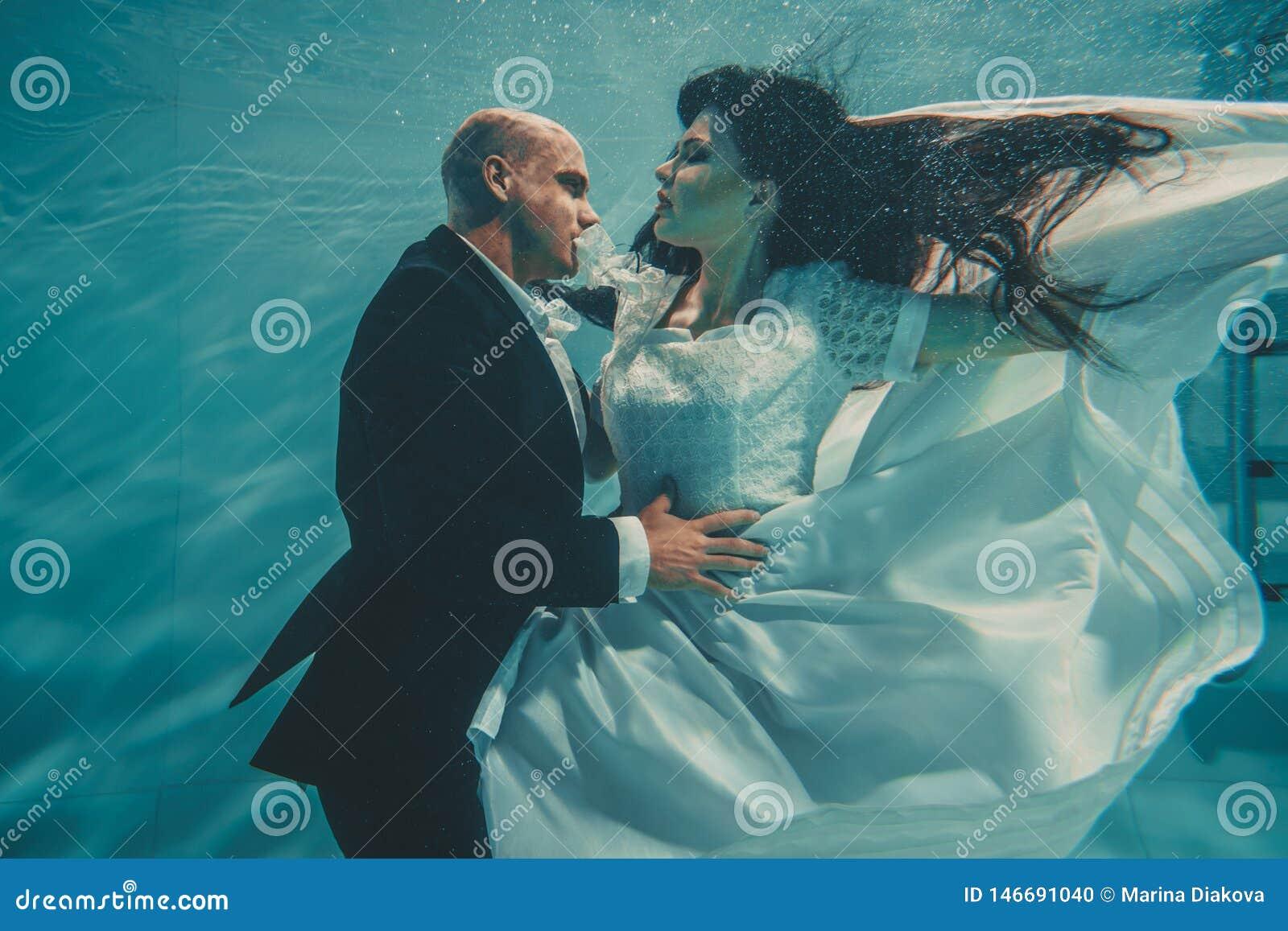 Το όμορφο ρομαντικό ζεύγος της νύφης και ο νεόνυμφος μετά από το γάμο που κολυμπούν ήπια κάτω από το νερό και χαλαρώνουν