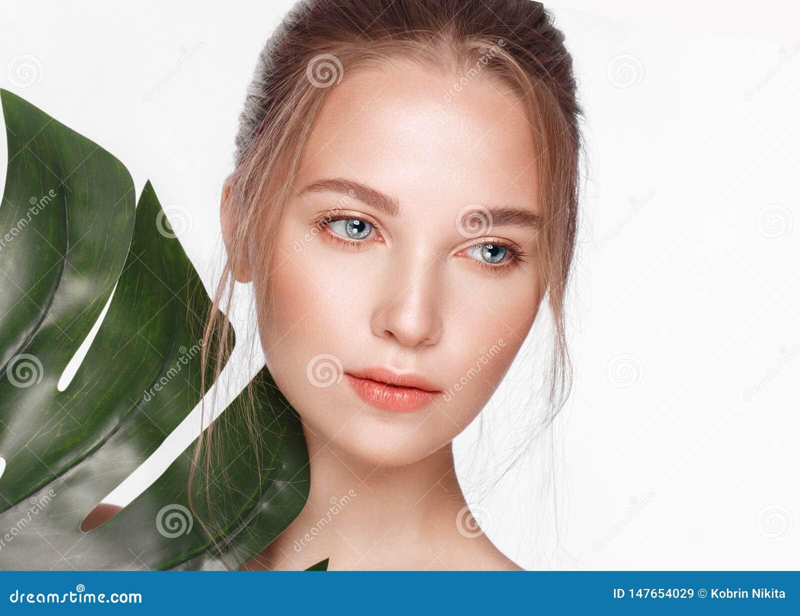 Το όμορφο φρέσκο κορίτσι με το τέλειο δέρμα, φυσικό κάνει τα επάνω και πράσινα φύλλα r