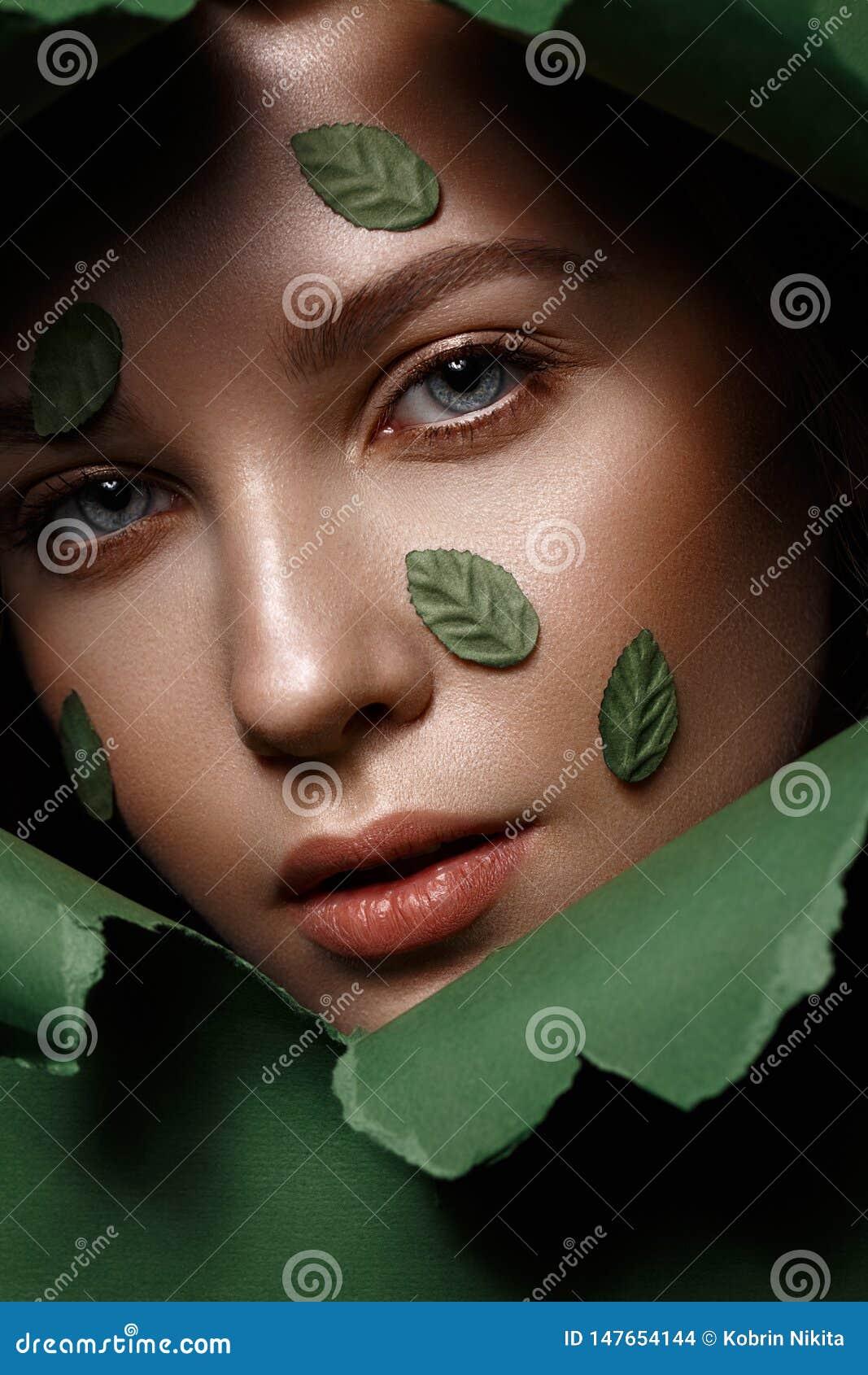 Το όμορφο φρέσκο κορίτσι με το τέλειο δέρμα, φυσικό κάνει τα επάνω και πράσινα φύλλα r o