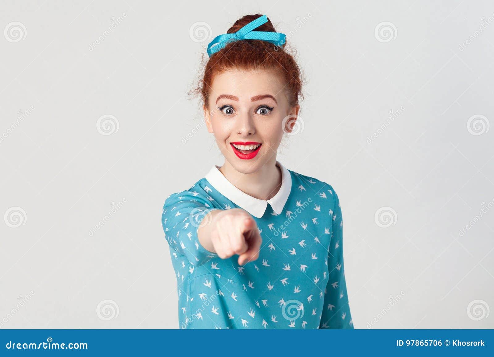 Το όμορφο redhead κορίτσι, που φορά το μπλε φόρεμα, ανοίγοντας τα στόματα ευρέως, που έχουν εκπλήξει που συγκλονίζονται εξετάζει,